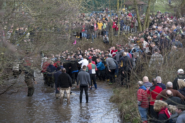 Opposing teams of the Up'ards and the Down'ards stand in water as they compete in the annual Royal Shrovetide Football Match in Ashbourne, Derbyshire, England on February 17, 2015.