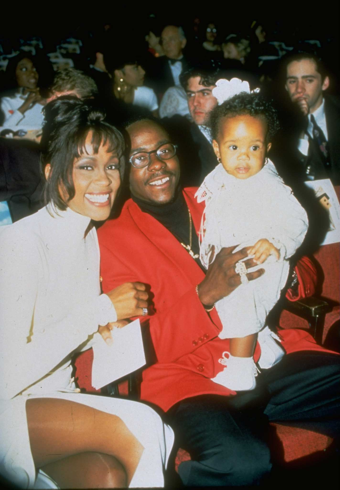 Whitney Houston sits with singer husband Bobby Brown who is holding their daughter Bobbi Kristina Brown in Jan. 1994.