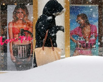 A pedestrian makes their way past a Victoria's Secret store along a snow covered street during a winter snowstorm in Boston
