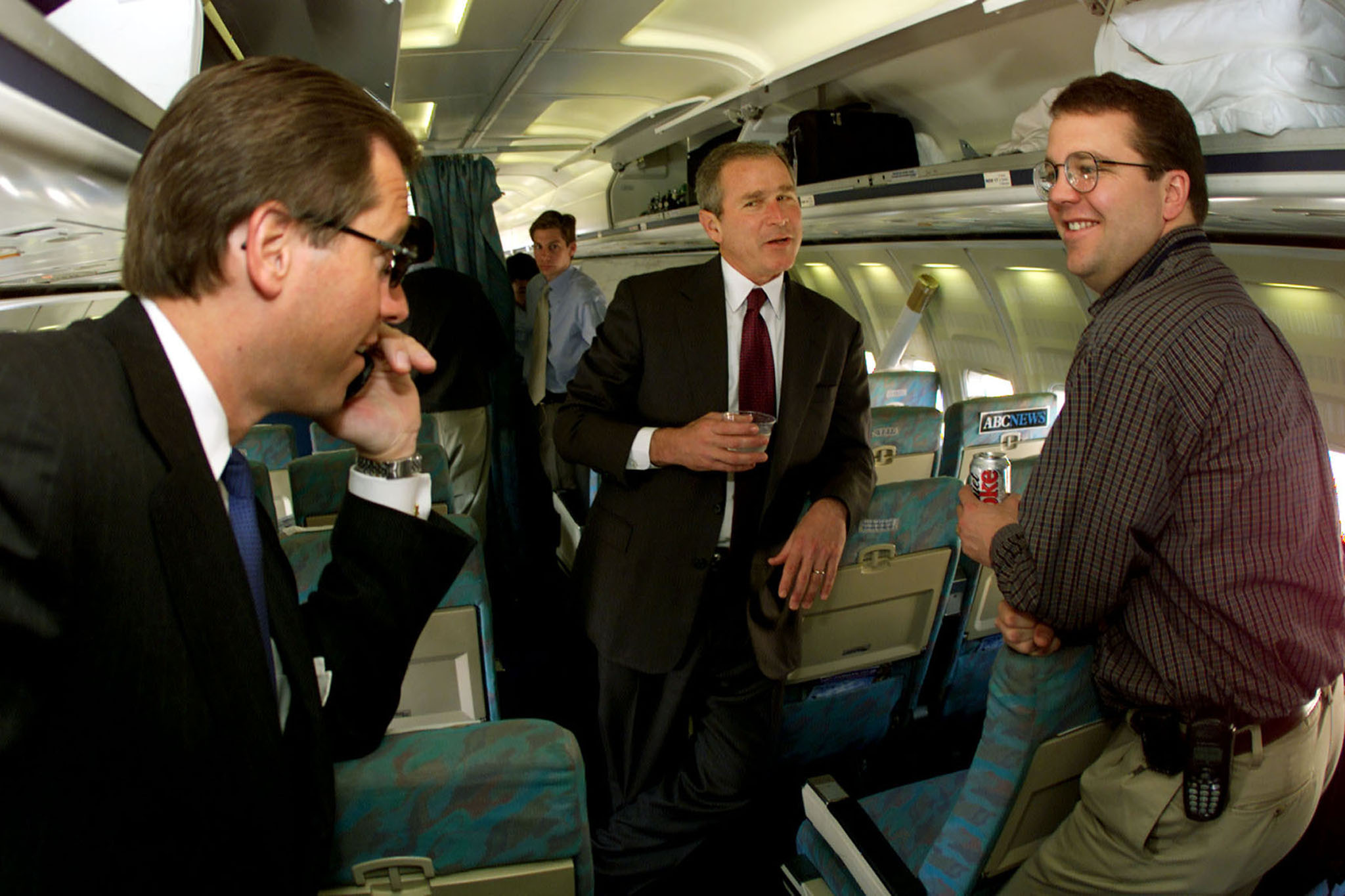From Left: Brian Williams, President George W. Bush and AP writer Glenn Johnson talk  aboard Bush's campaign plane in Florence S.C. on Feb. 17, 2000.