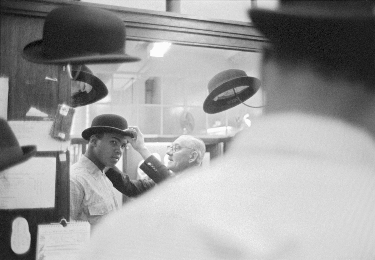 Ali in London, 1963                               Brian Seed:  Cassius Clay went on a shopping spree in June 1963, when he was in London to fight British boxer Henry Cooper. Cassius won the fight. Here he is being fitted for a bowler hat. The hatter told Clay that his head was lopsided.  Brian Seed is a photographer whose work has appeared in TIME, LIFE and Sports Illustrated magazines.