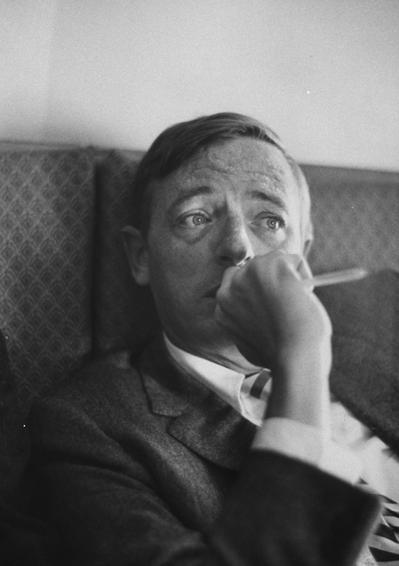William F. Buckley Jr., riding in airplane en route to Washington DC, in 1965