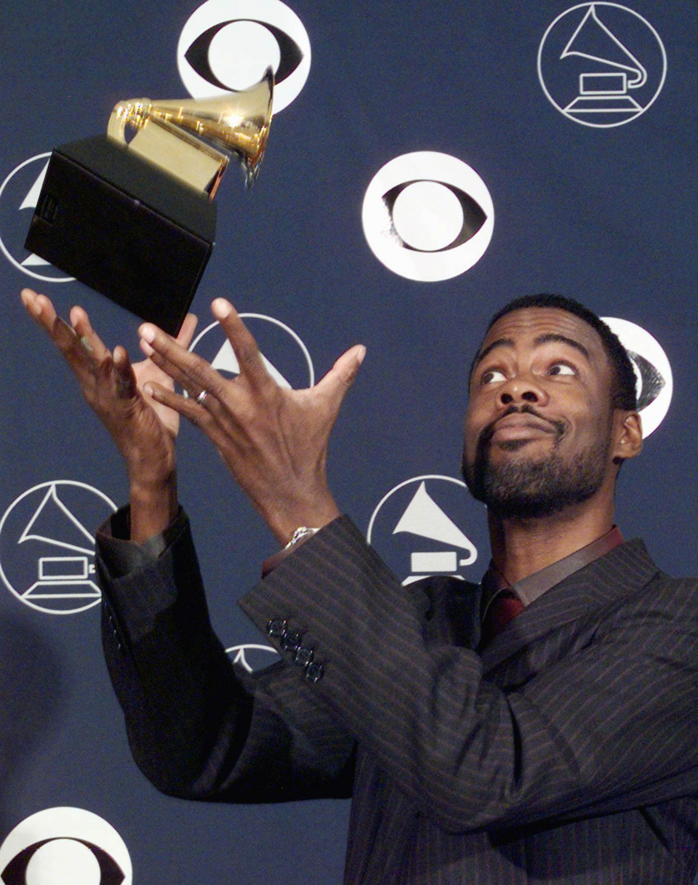 Comedian Chris Rock throws his Grammy Award in the