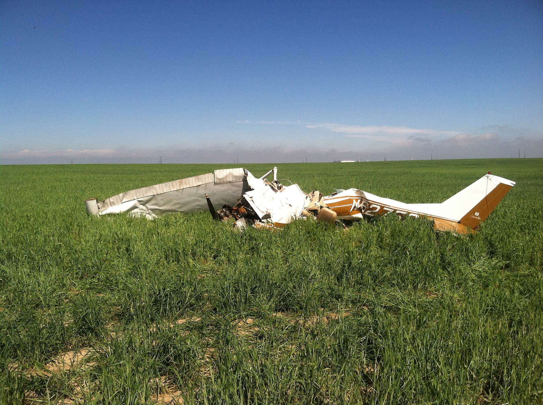The wreckage of a crashed Cessna 150 airplane lies in a field near Watkins, Co. on May 31, 2014.