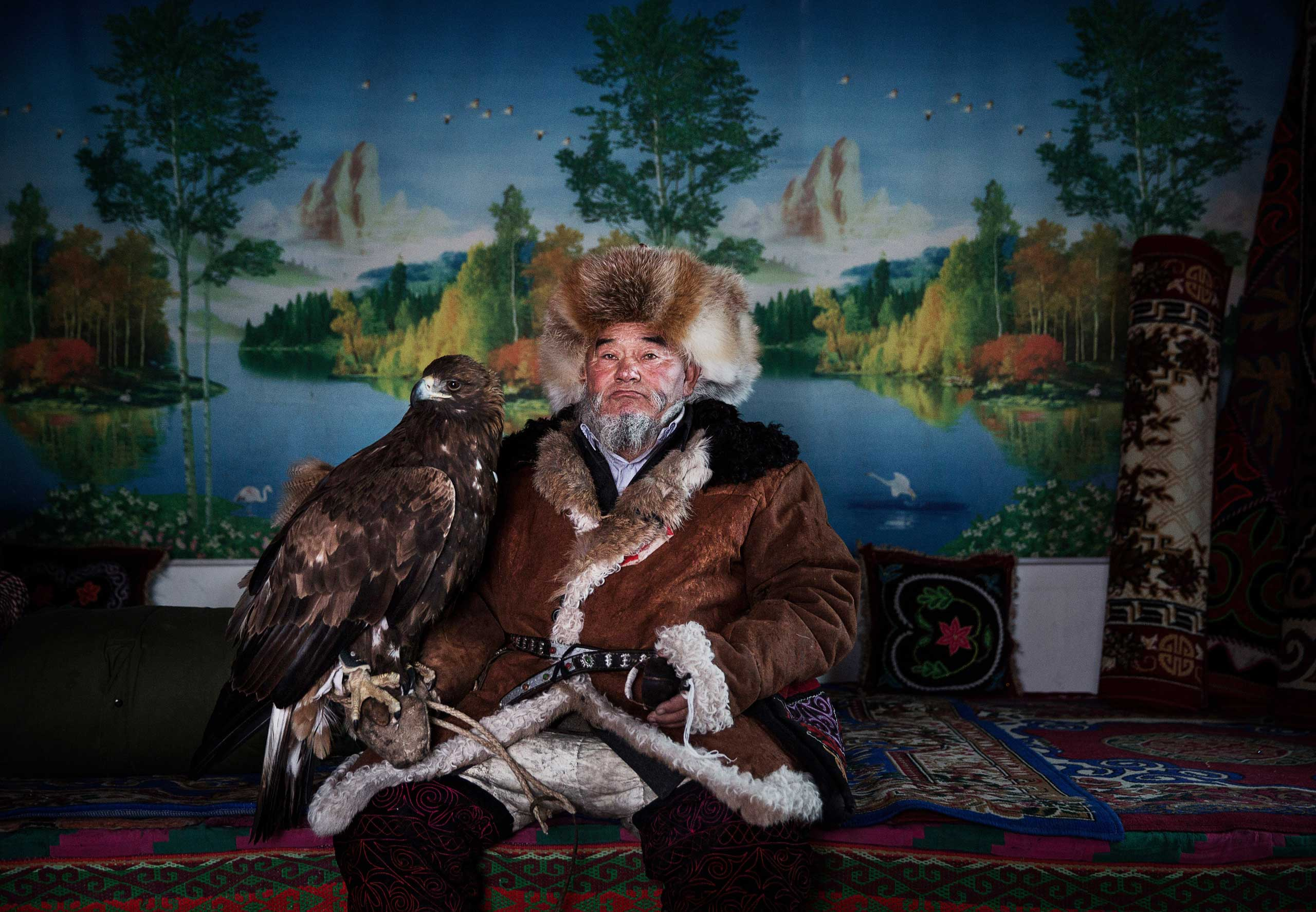 Chinese Kazakh eagle hunter Margars Mazkin, 74, sits with his eagle before leaving for competition on Jan. 31, 2015 in the mountains of Qinghe County, Xinjiang, northwestern China.