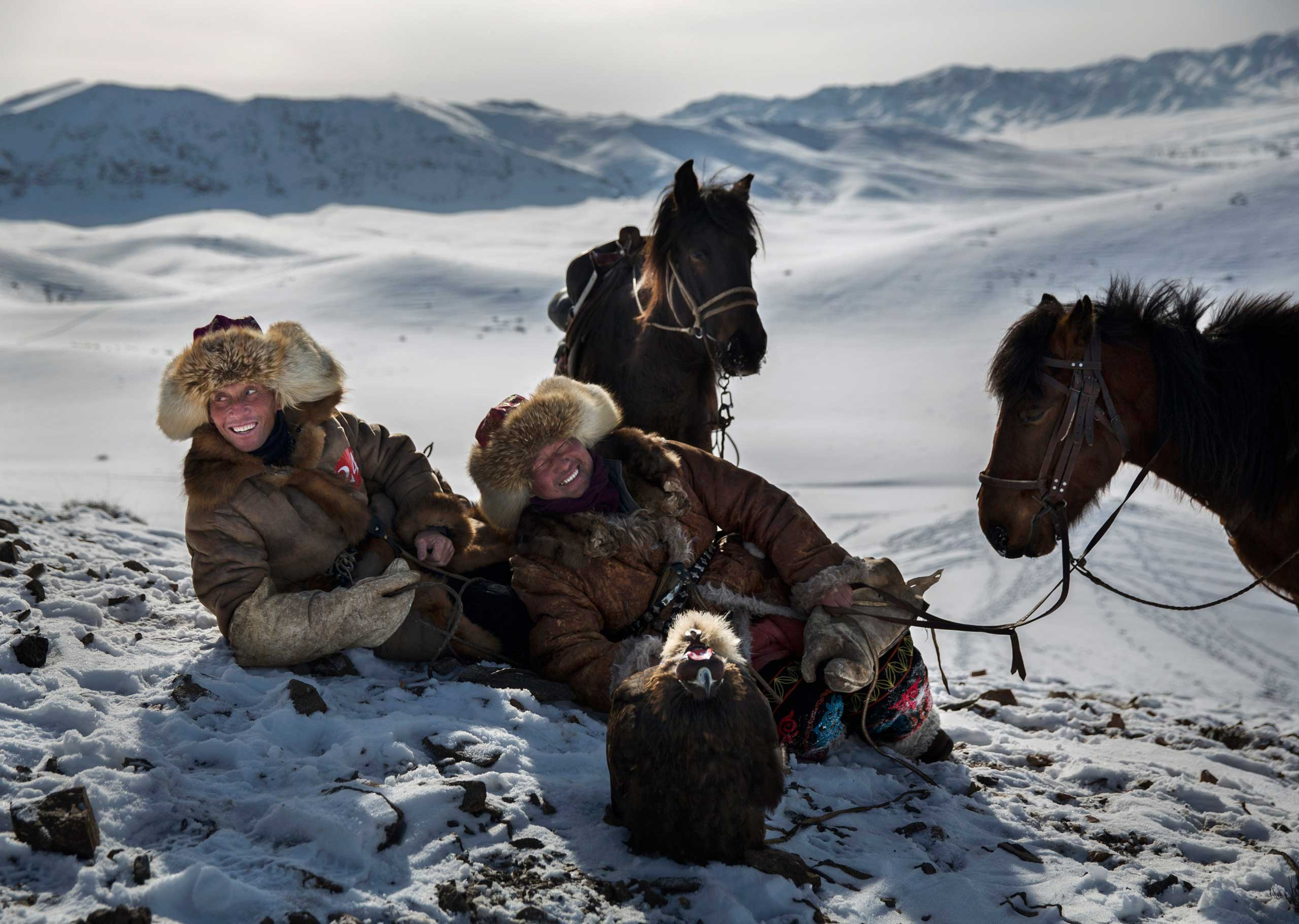 Chinese Kazakh eagle hunters laugh together as they rest during the competition.