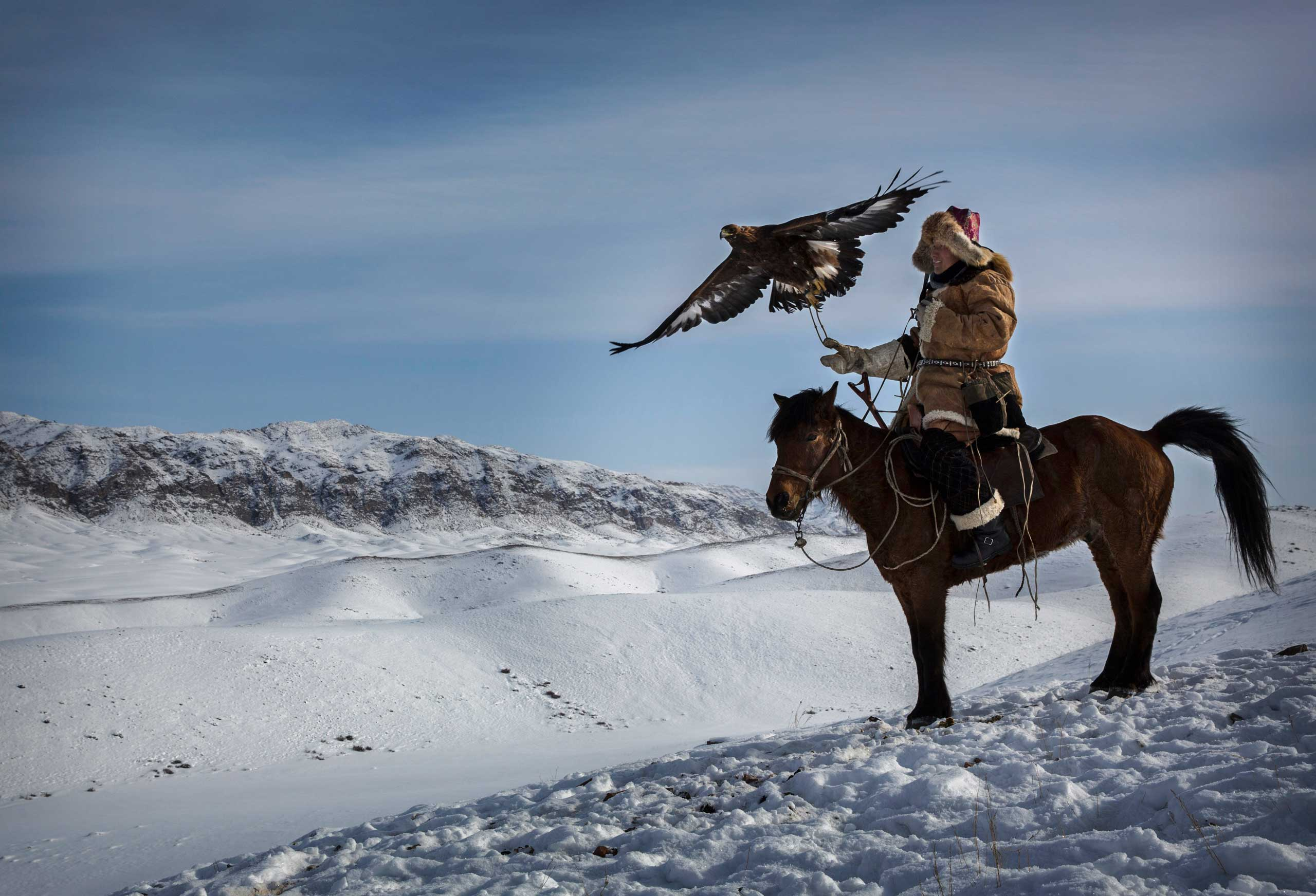 Chinese Kazakh eagle hunter releases his eagle during the competition in the mountains of Qinghe County, Xinjiang, northwestern China.