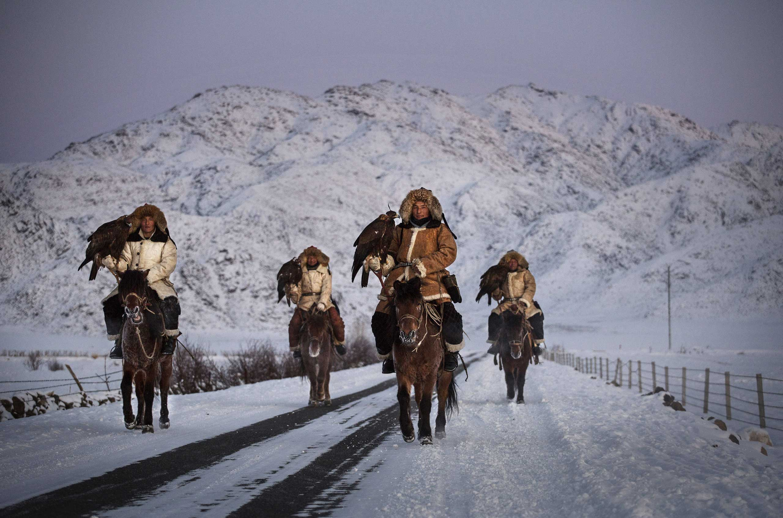 Chinese Kazakh eagle hunters from the Beysenbay family who are all brothers ride together with their eagles before the competition  in the mountains of Qinghe County, Xinjiang.