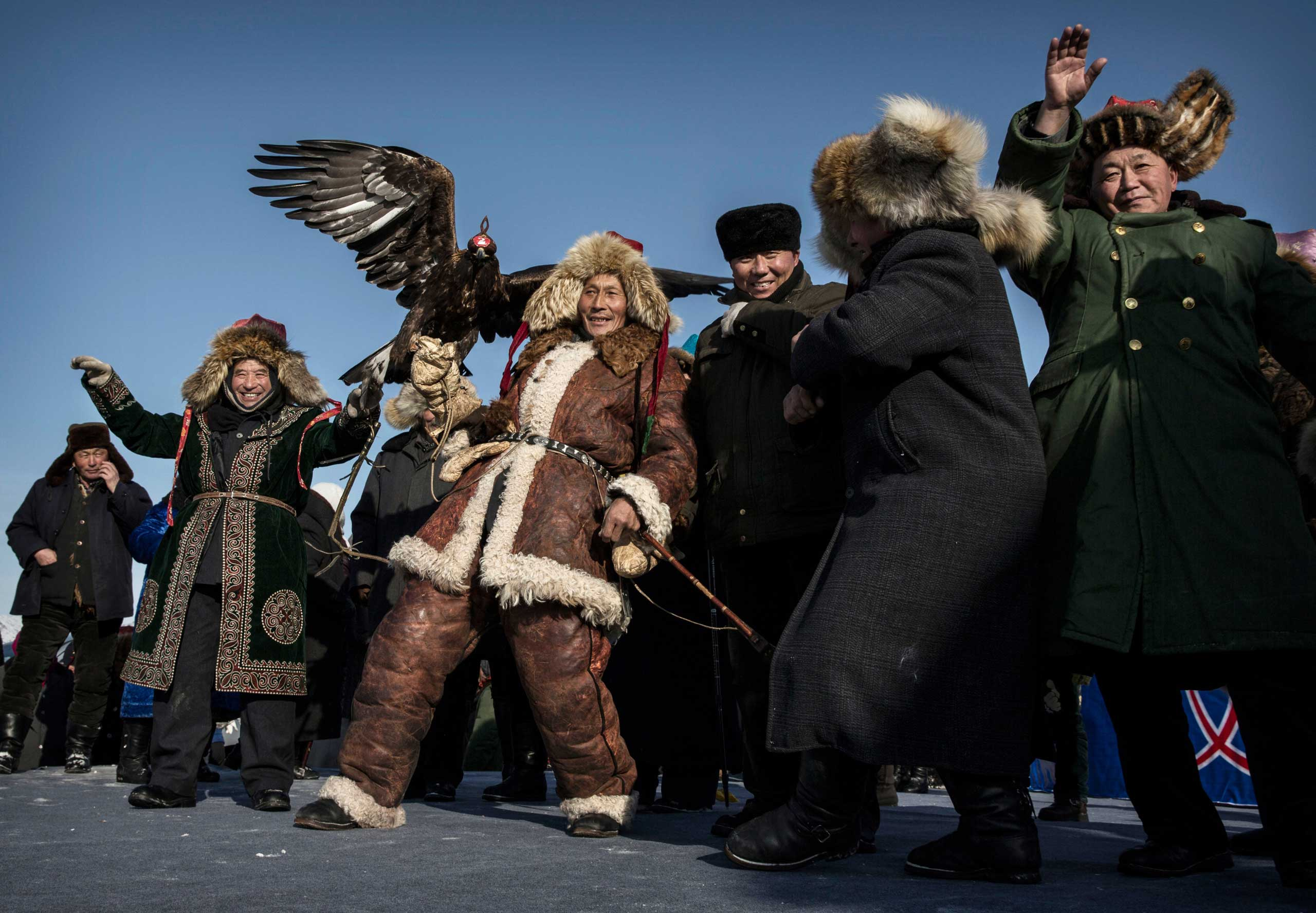 A Chinese Kazakh eagle hunter dances with horsemen before the competition.