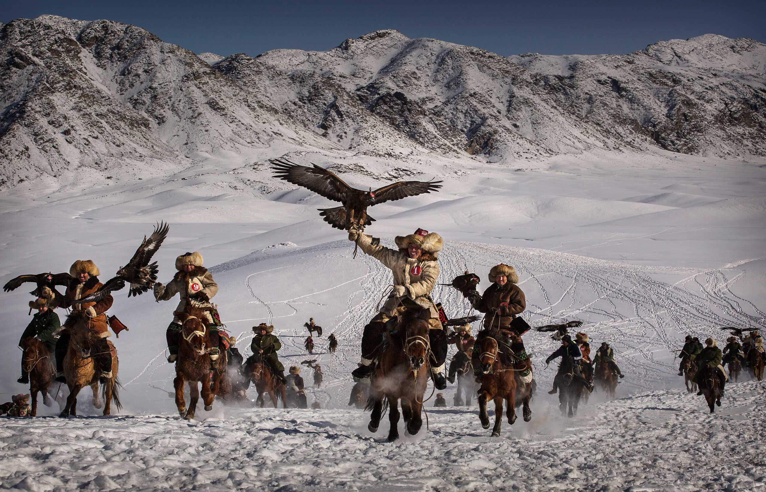 Chinese Kazakh eagle hunters ride with their eagles during the competition.