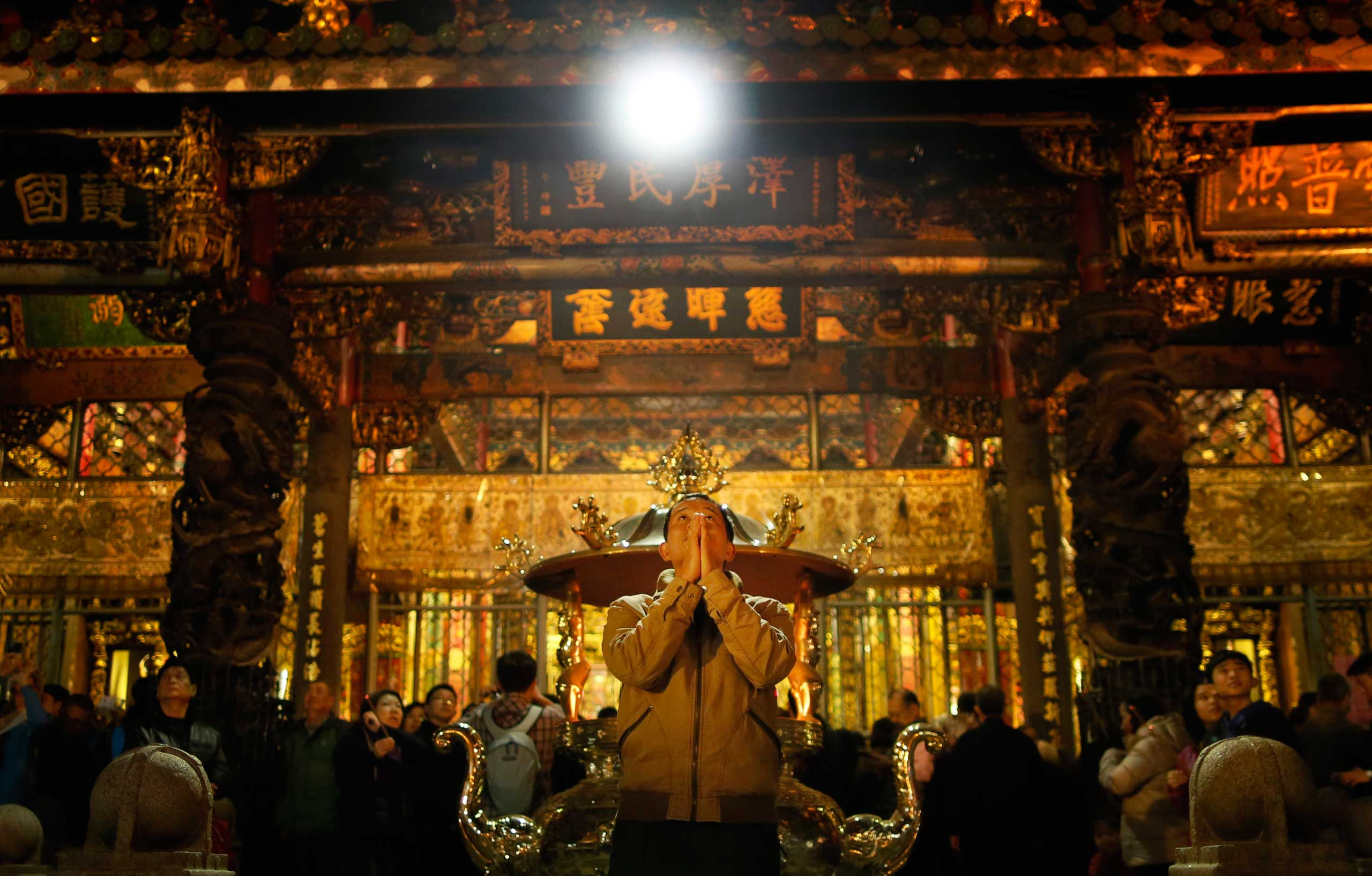 A devotee prays on the eve of the Lunar New Year at the Lungshan Temple in Taipei, Taiwan, Feb. 18, 2015.
