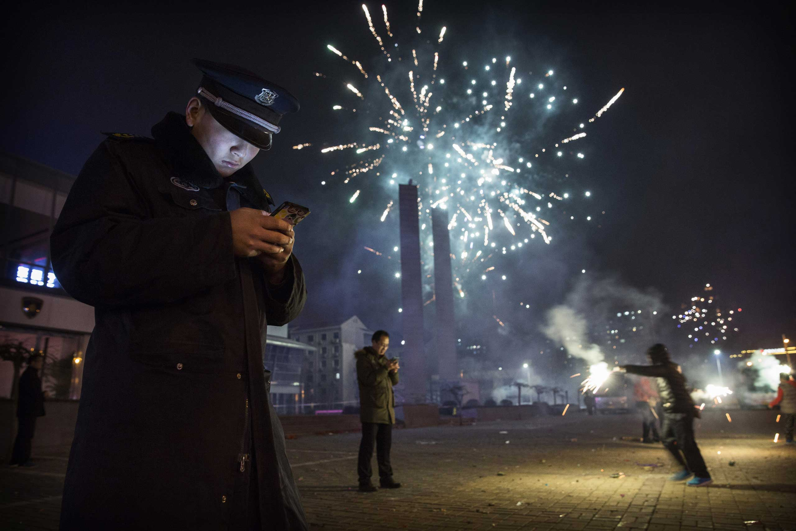 A security guard checks his smartphone as fireworks explode during celebrations of the Lunar New Year early on Feb. 19, 2015 in Beijing.