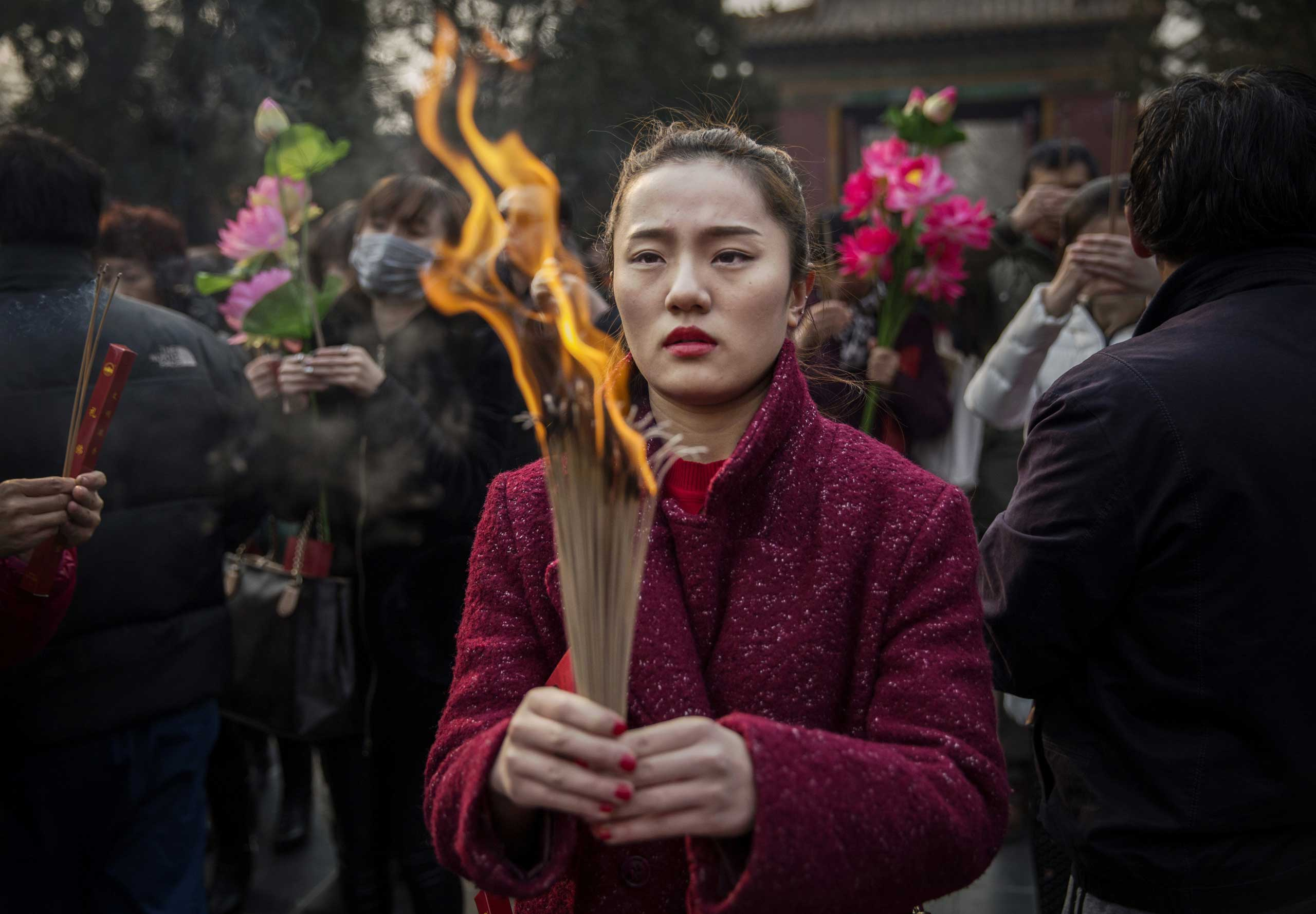 Woman holds incense while praying with others at the Yonghegong Lama Temple during celebrations for the Lunar New Year, Feb. 19, 2015 in Beijing.