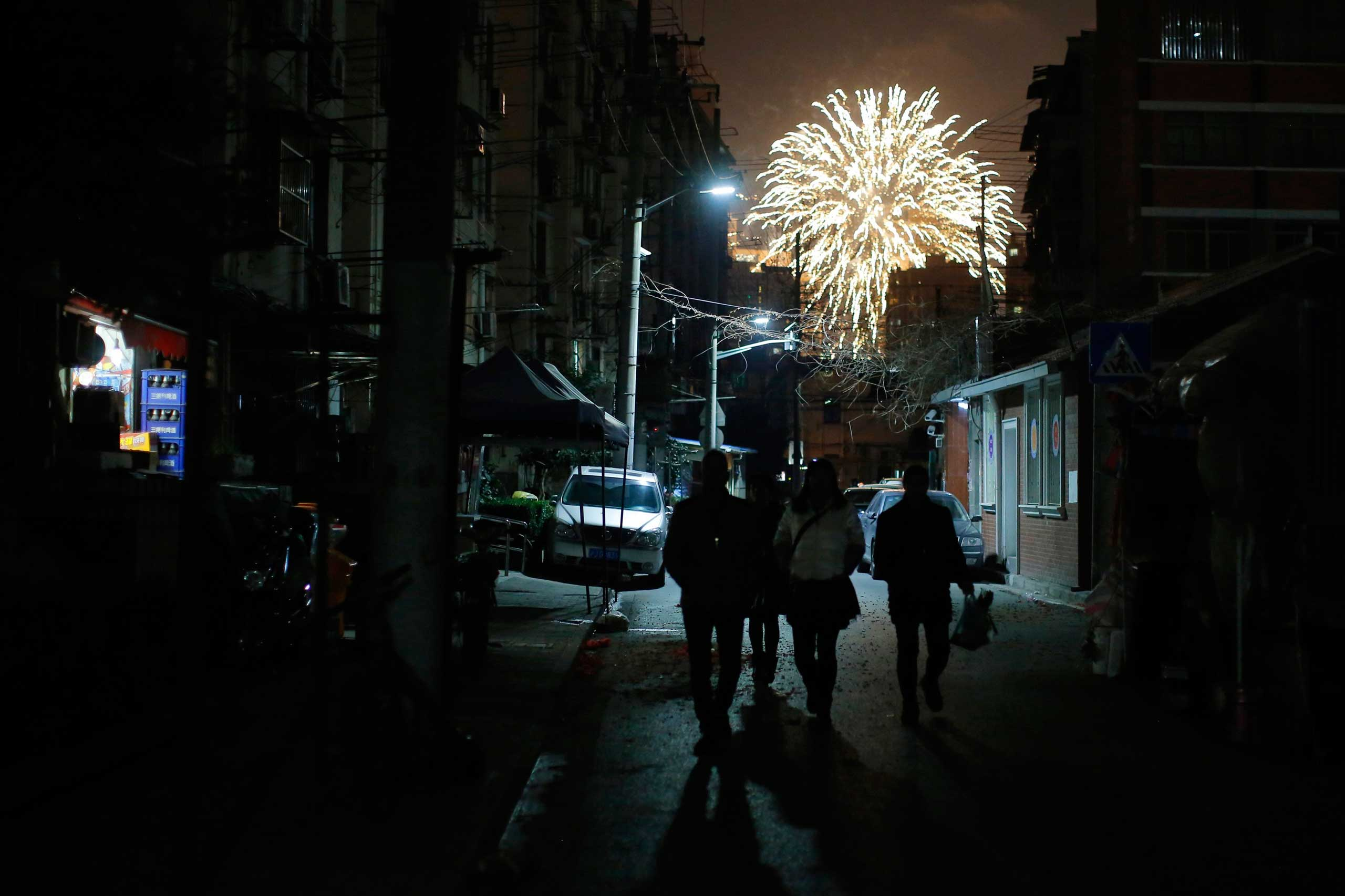 People walk as residents set off fireworks as part of Lunar New Year celebrations in Shanghai, Feb. 19, 2015.