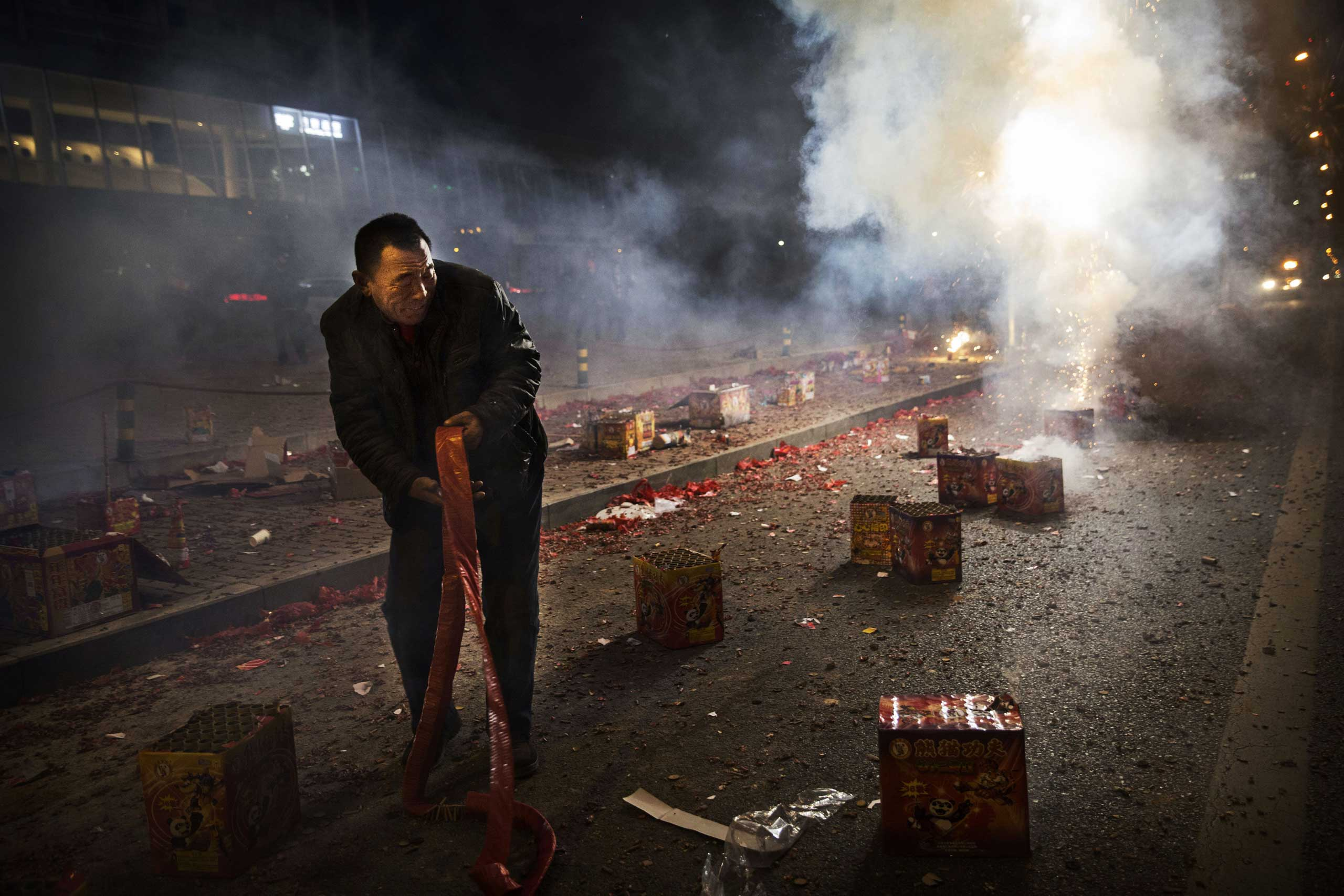 A man reacts as firecrackers he lit explode during celebrations of the Lunar New Year early on Feb. 19, 2015 in Beijing.