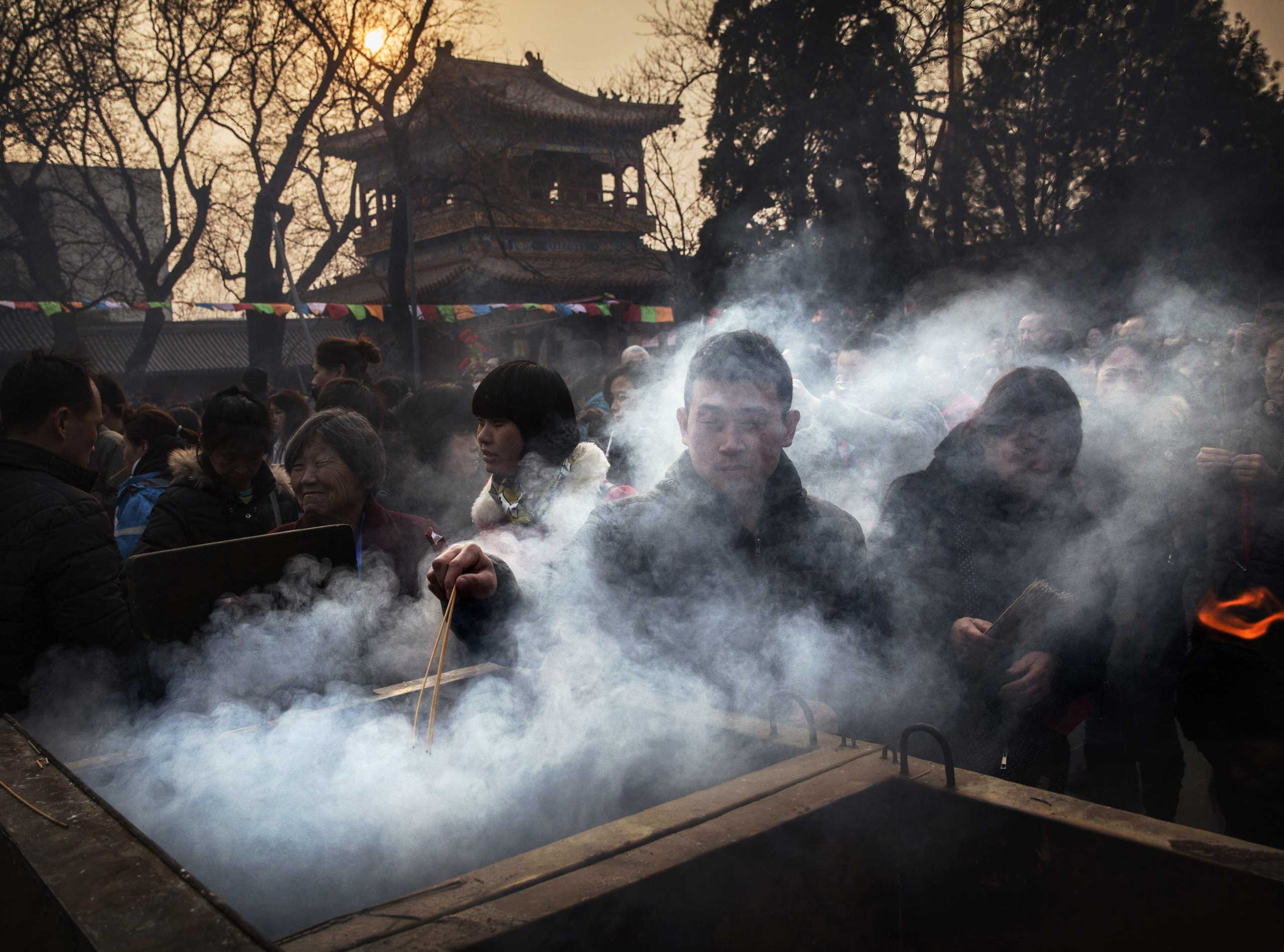 A man is shrouded in smoke from incense as he lights a stick while praying with others at the Yonghegong Lama Temple during celebrations for the Lunar New Year, Feb. 19, 2015 in Beijing.