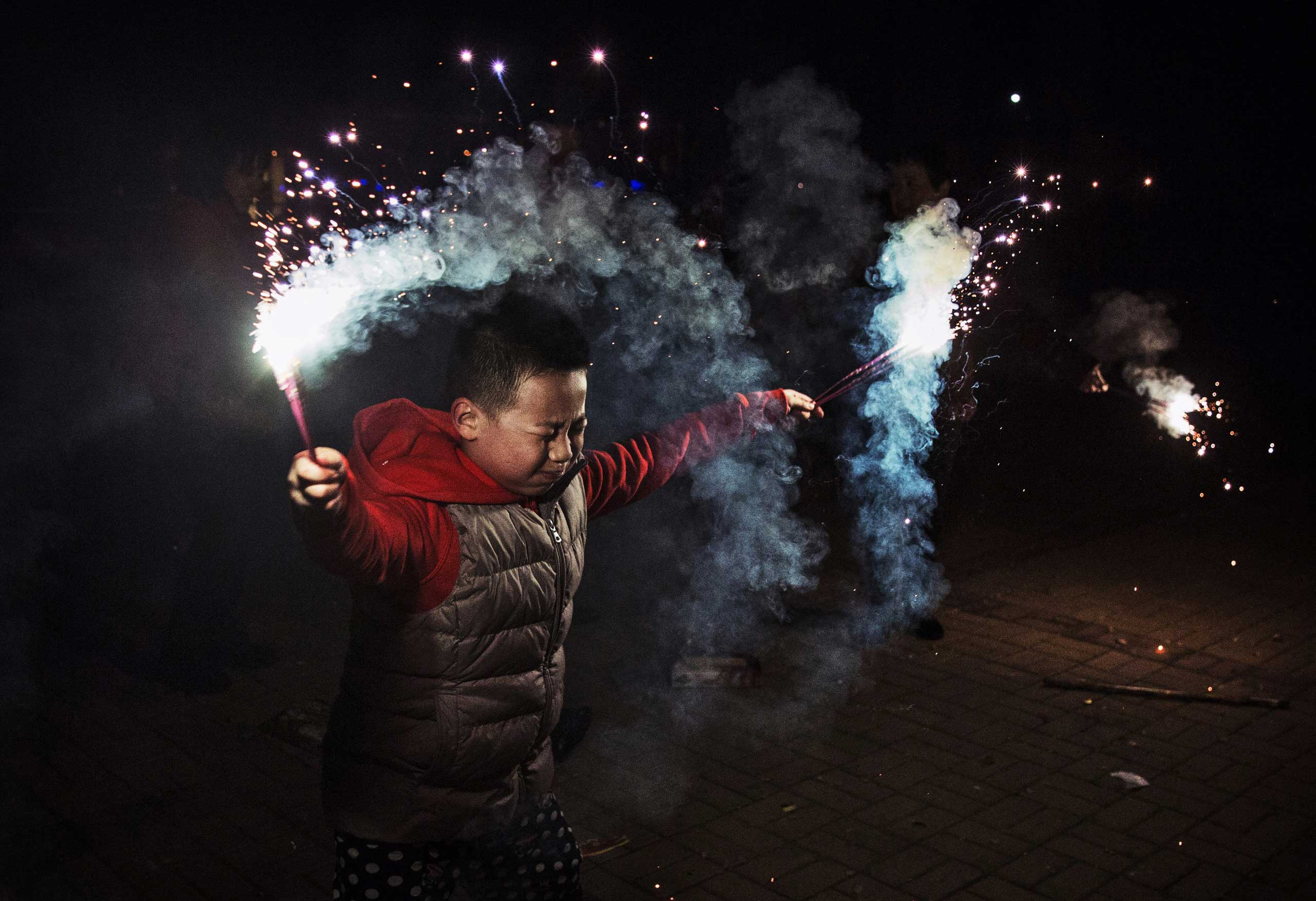 A boy uses sparklers during celebrations of the Lunar New Year early on Feb. 19, 2015 in Beijing.