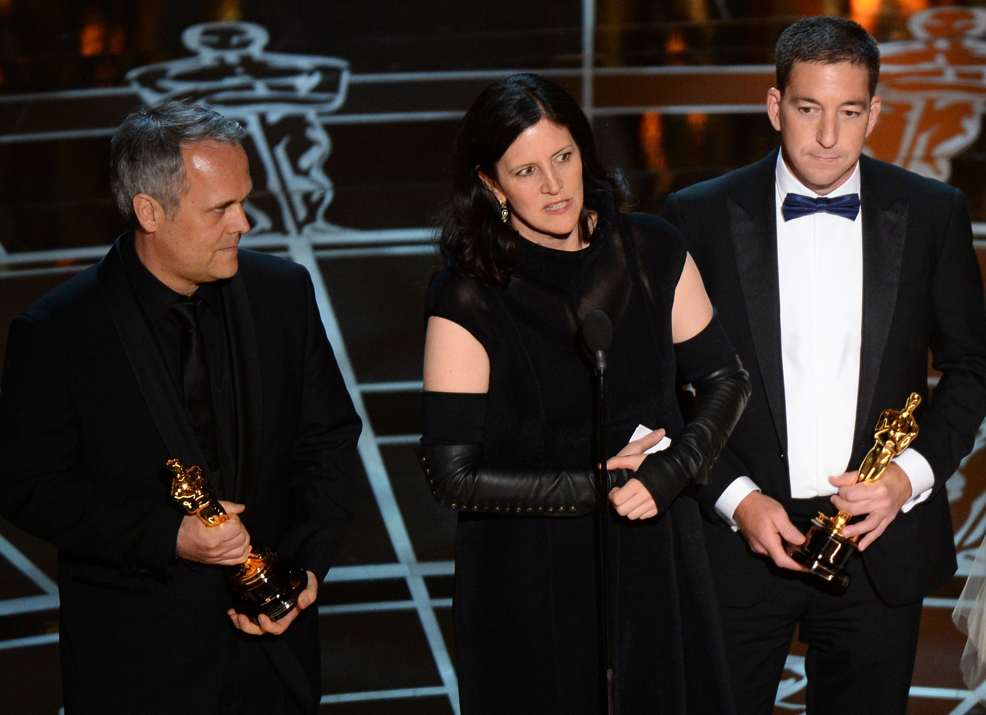 Winners for Best Documentary Feature CitizenFour Laura Poitras, center, and Dirk Wilutzky, left, give their acceptance speech flanked by Glenn Greenwald  at the 87th Oscars Feb. 22, 2015 in Hollywood, Calif.