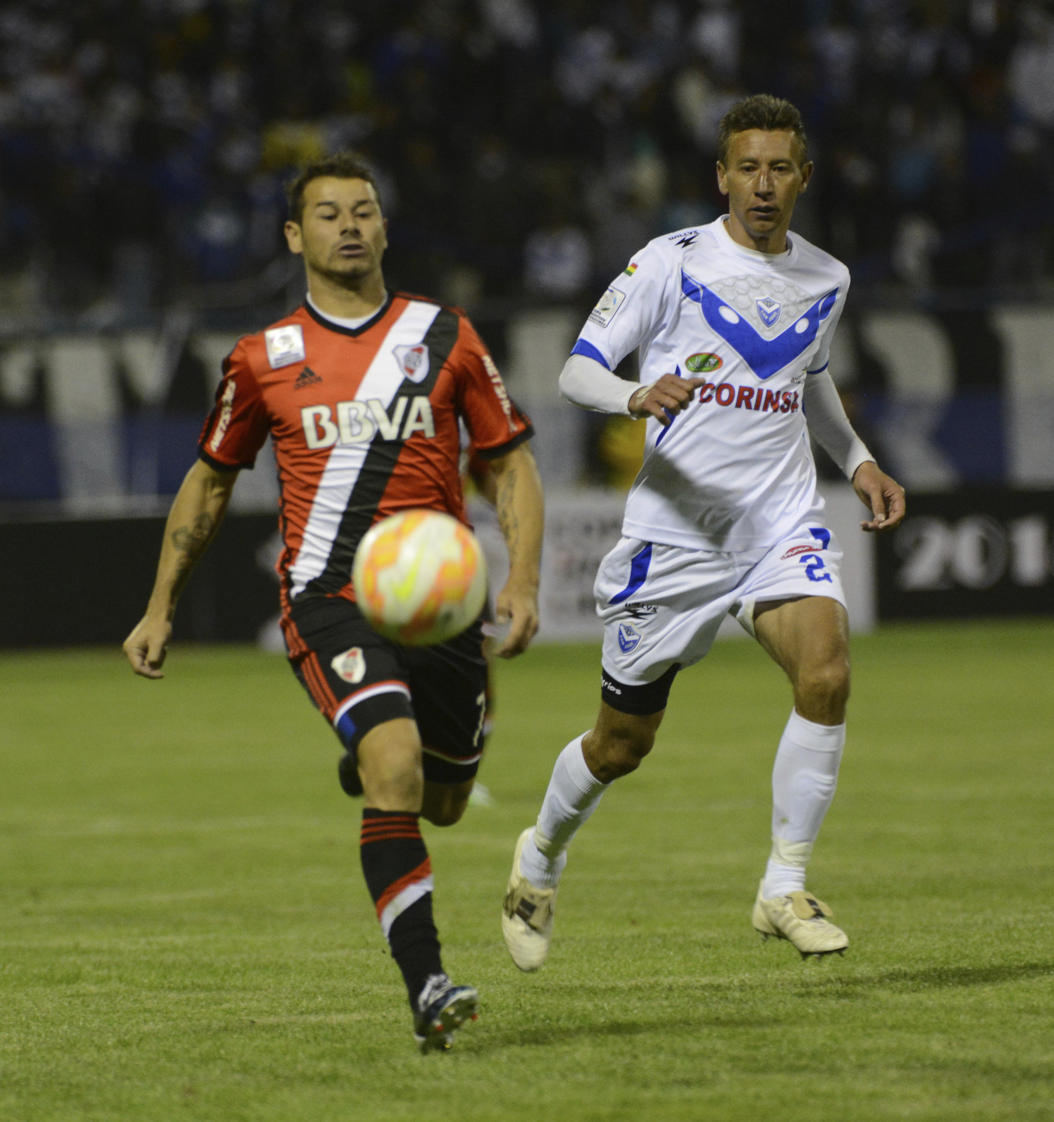 Rodrigo Mora of River (L) and Arnaldo Vera of San Jose (R) run for the ball during a match between San Jose and River Plate as part of group stage Copa Bridgestone Libertadores 2015 at Jesus Bermudez Stadium on February 19, 2015 in Oruro, Bolivia.