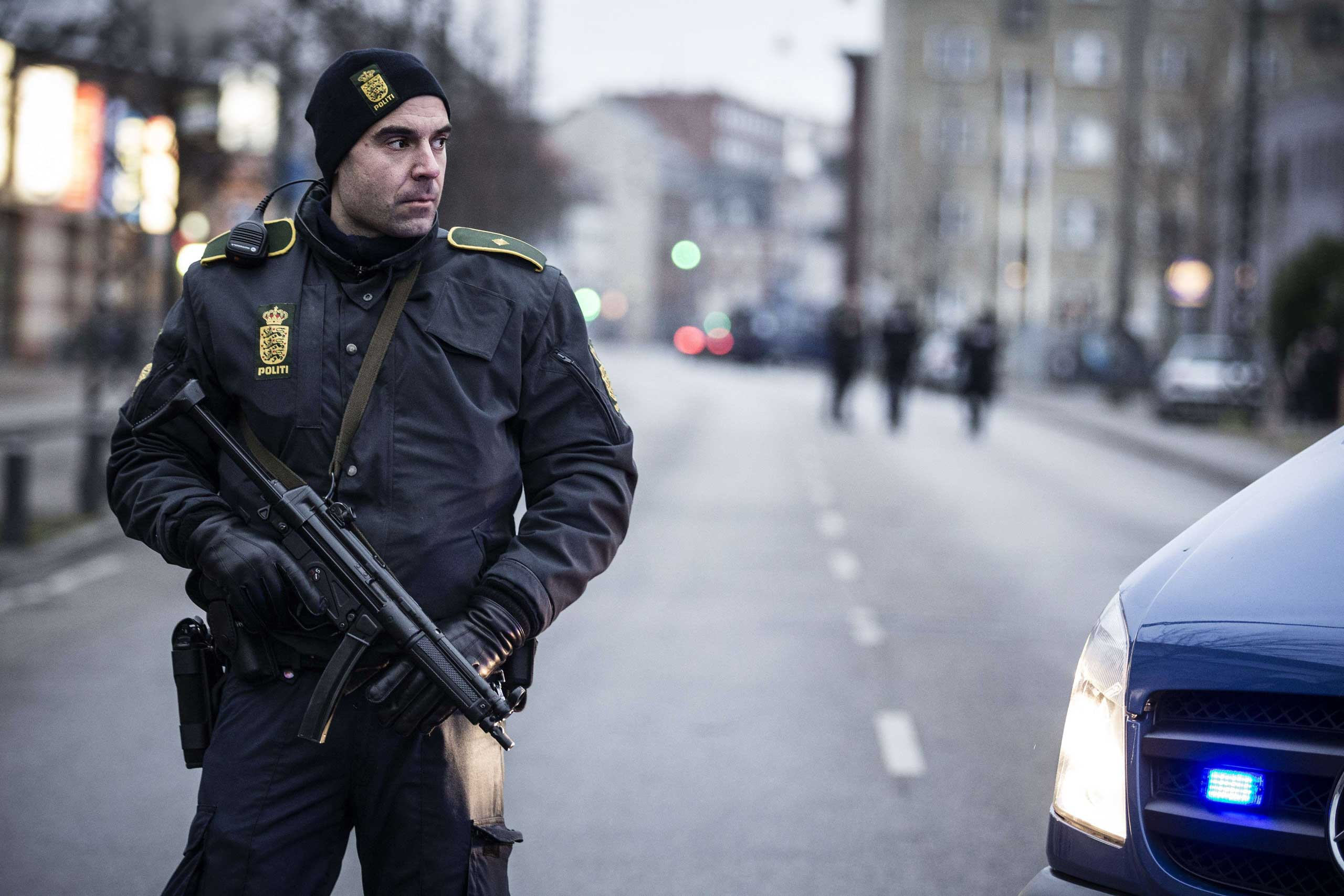 A police officer guards the street around the Noerrebro train station in Copenhagen on Feb. 15, 2015 where a man has been shot in a police action following two fatal attacks in the Danish capital.
