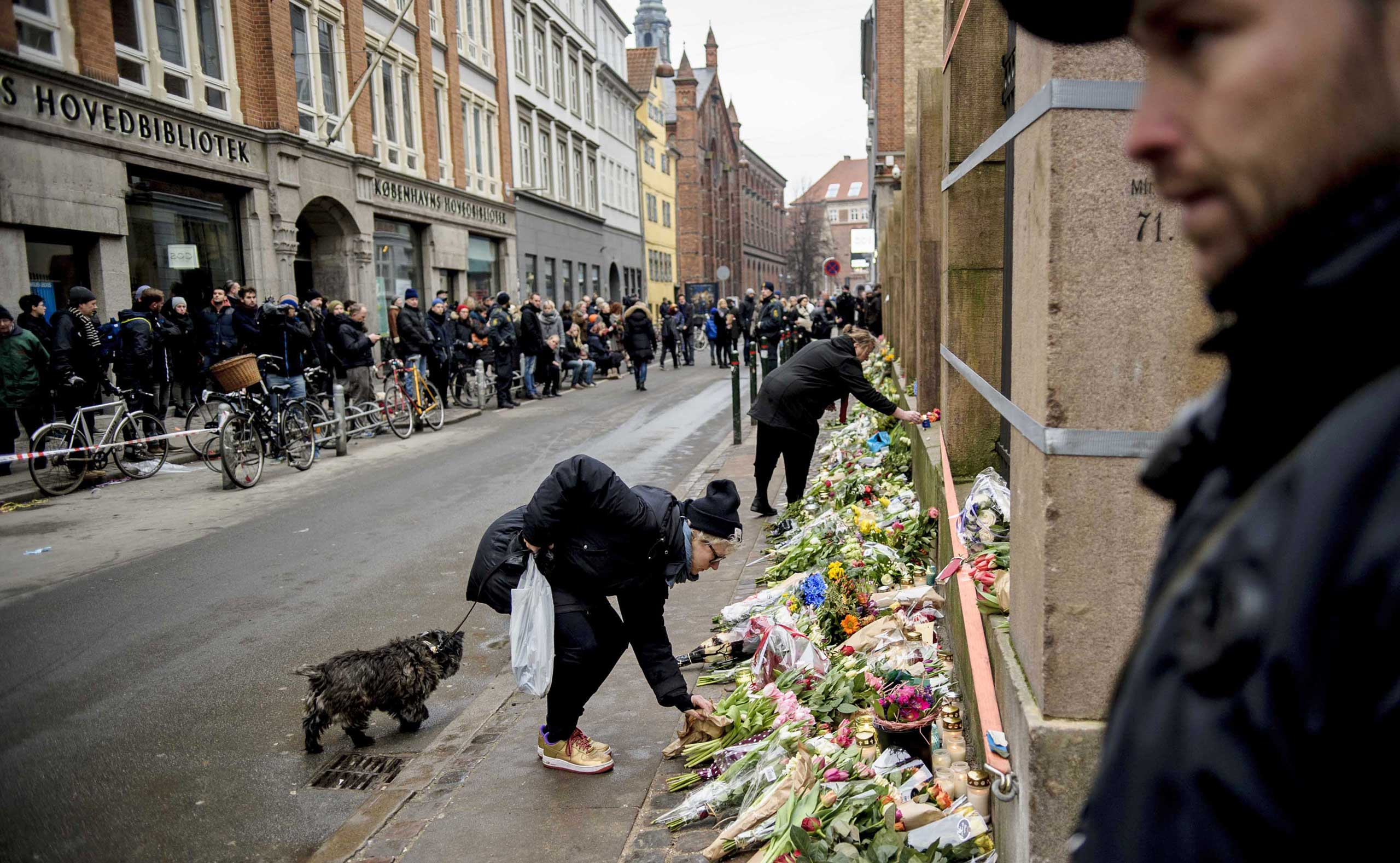People lay flowers outside a synagogue where an attack took place in Copenhagen on Feb. 15, 2015