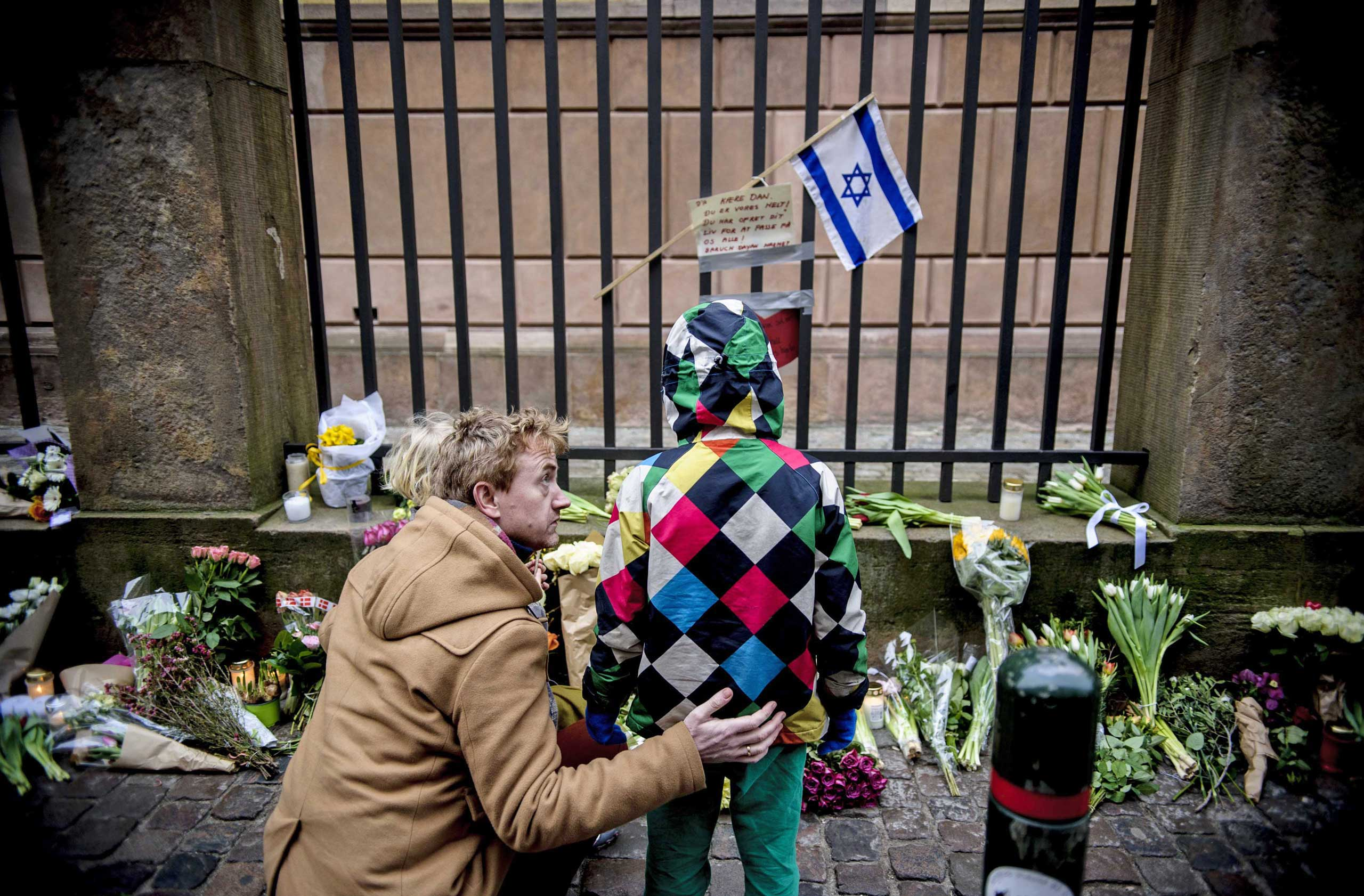 People look at flowers placed outside a synagogue where an attack took place in Copenhagen, Feb. 15, 2015.