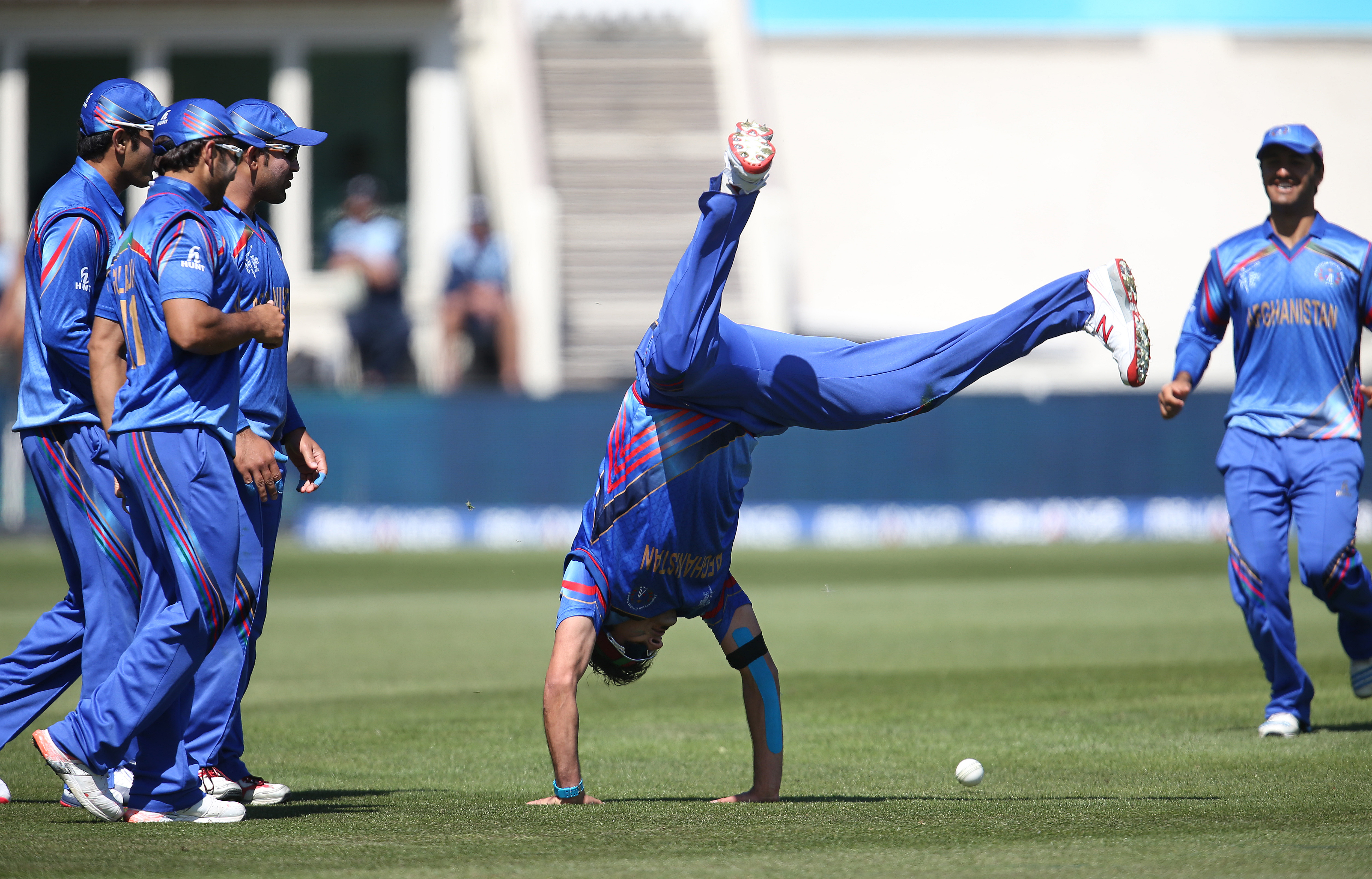 Afghanistan's Hamid Hassan is watched by his teammates as he performs a hand-stand after taking a catch to dismiss Scotland's Josh Davey during their Cricket World Cup Pool A match in Dunedin, New Zealand, Thursday, Feb. 26, 2015.