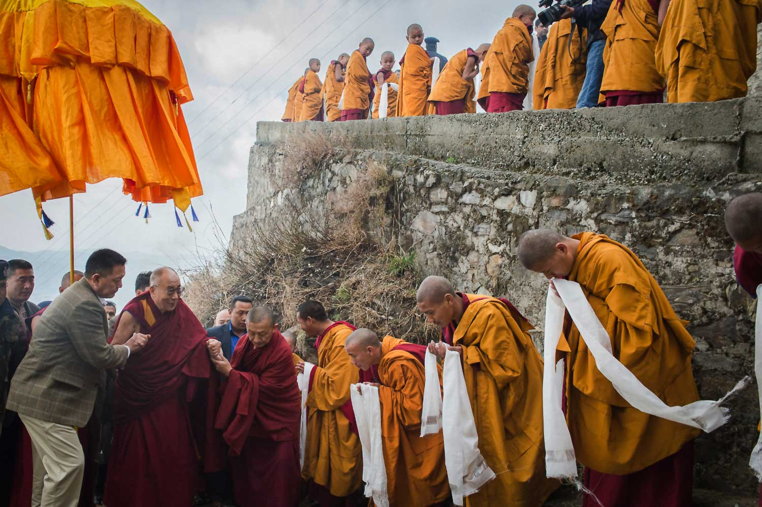 Tibetan Buddhist monks holding ceremonial scarfs stand in a line to welcome the Dalai Lama as he arrives at the Jhonang Takten Phuntsok Choeling monastery in Shimla, India, in March 2014.