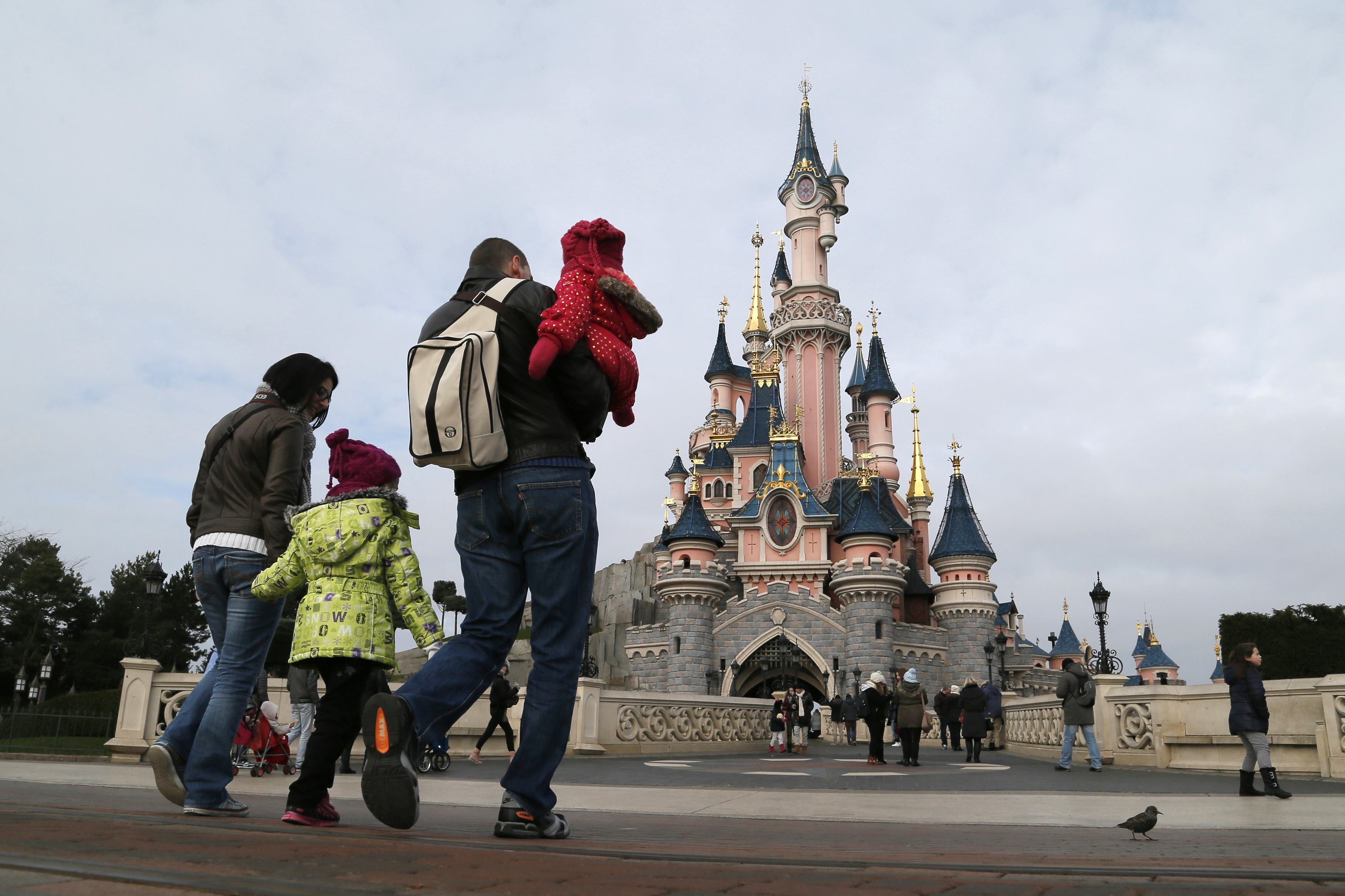Visitors walk towards the Sleeping Beauty Castle during a visit to the Disneyland Paris Resort run by EuroDisney S.C.A in Marne-la-Vallee on Jan. 21, 2015.