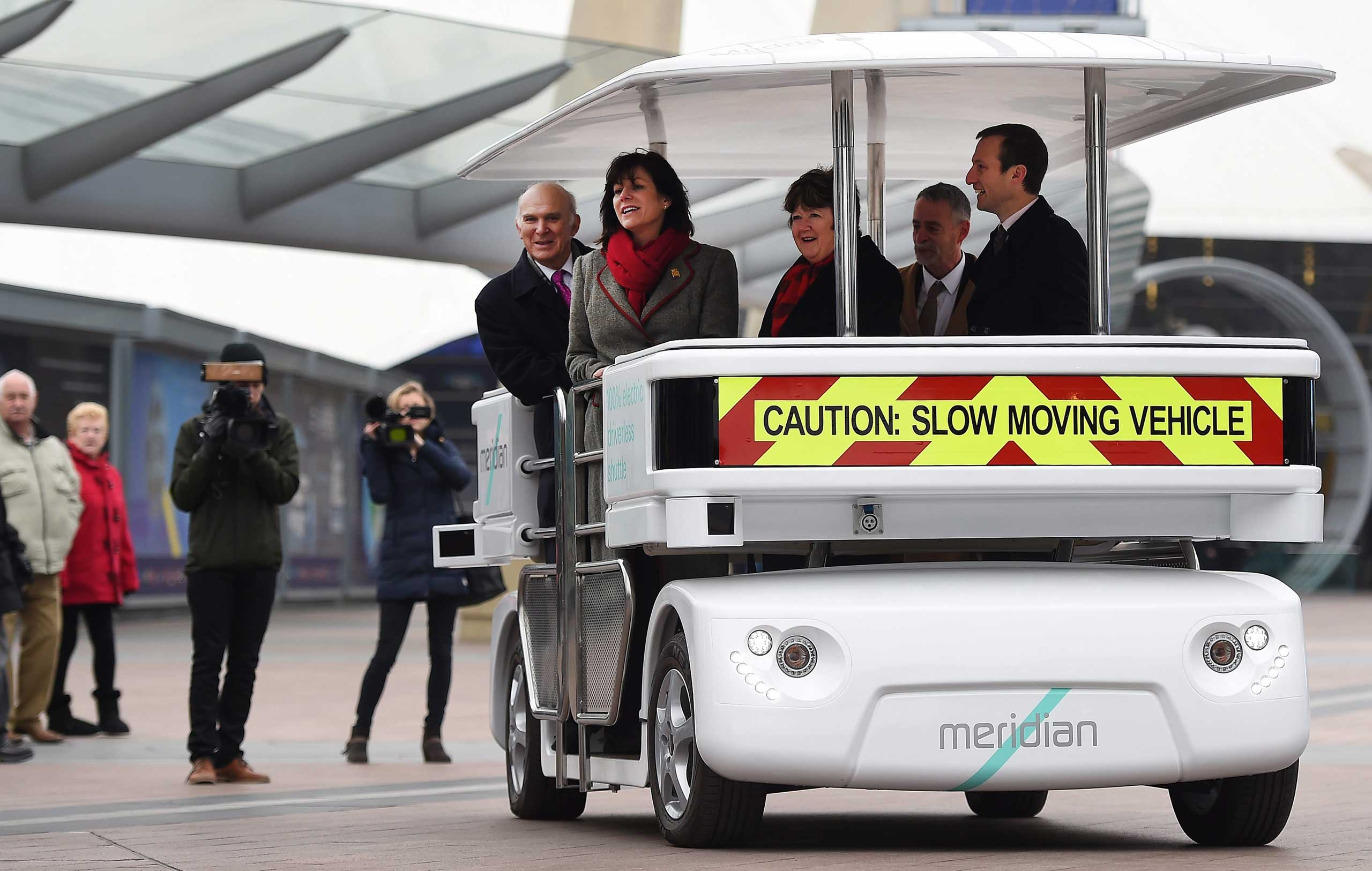 British Transport Minister Claire Perry and British Secretary of State for Business Innovation and Skills Vince Cable ride a driverless 'Meridian' vehicle in London, Feb. 11,2015.