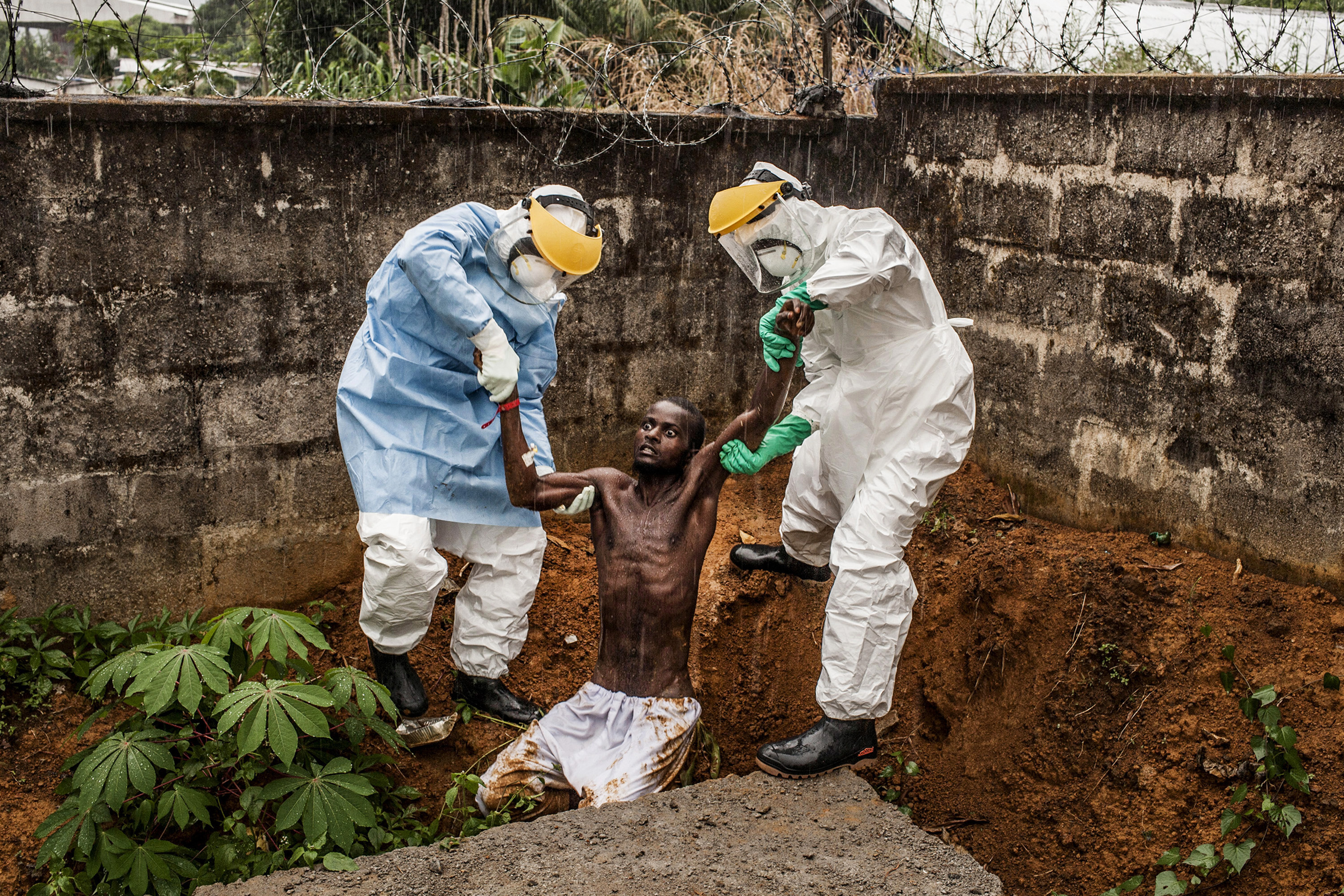 National Geographic: How Ebola Found Fertile Ground in Sierra Leone's Chaotic CapitalAt Sierra Leone's Hastings Ebola Treatment Center, staff help a man suffering from Ebola-induced delirium after he fled the isolation ward and tried to escape. Mental breakdowns are common in advanced Ebola. The man died about 12 hours later.