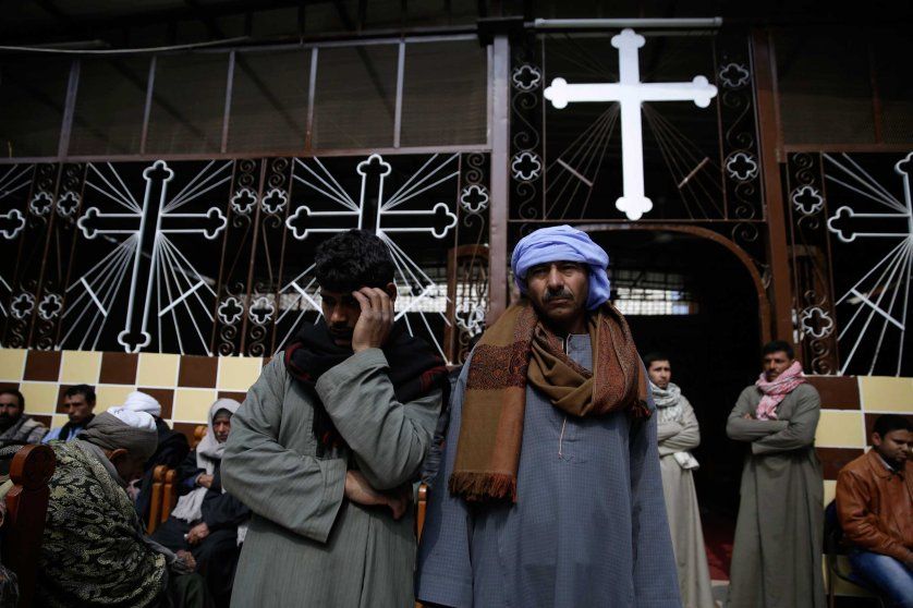 Men mourn over the Egyptian Coptic Christians who were captured in Libya and killed by militants affiliated with the Islamic State group, at the Virgin Mary church in the village of el-Aour, near Minya, 135 miles south of Cairo, Feb. 16, 2015.