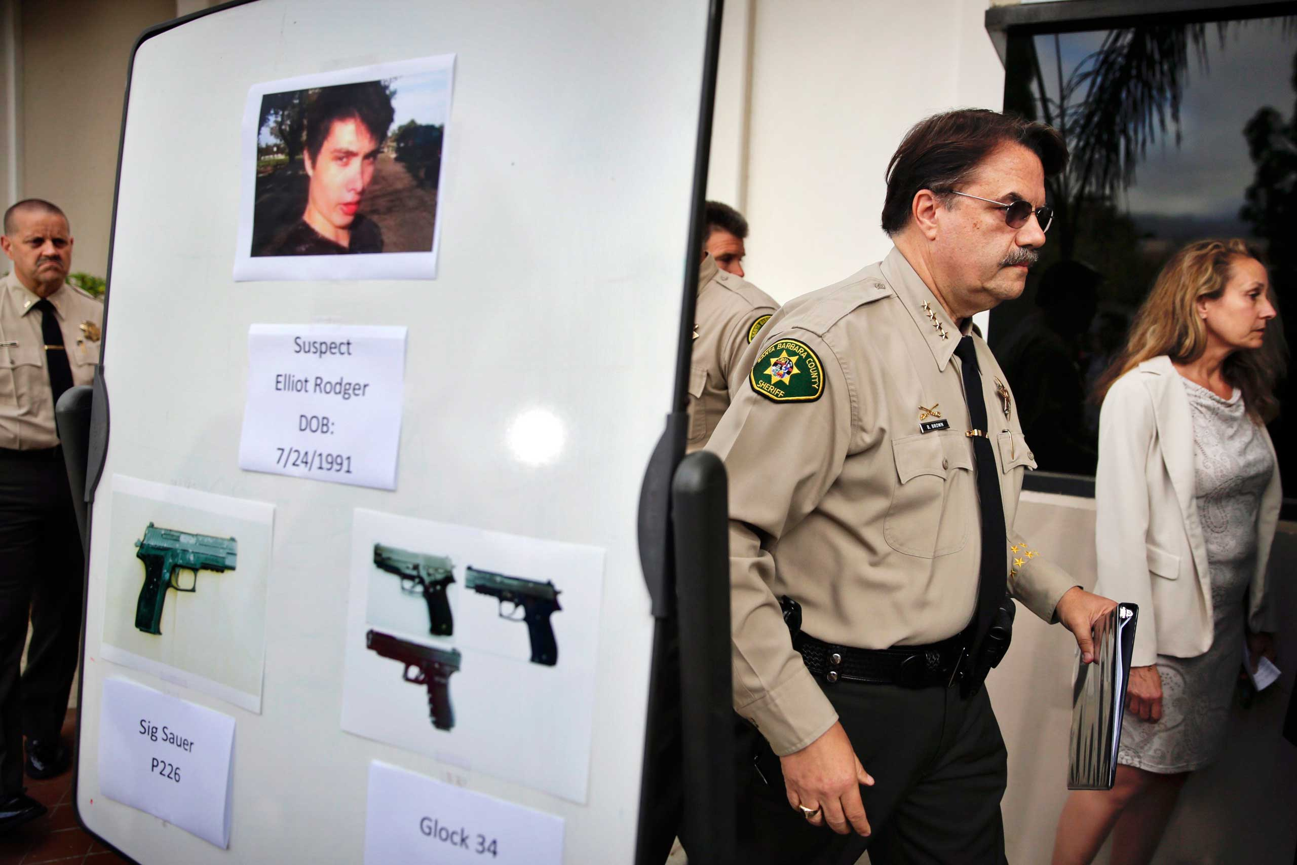 Santa Barbara County Sheriff Bill Brown, right, walks past a board showing the photos of gunman Elliot Rodger and the weapons he used in the mass shooting that took place in Isla Vista, Calif., after a news conference in Santa Barbara, Calif. on May 24, 2014.