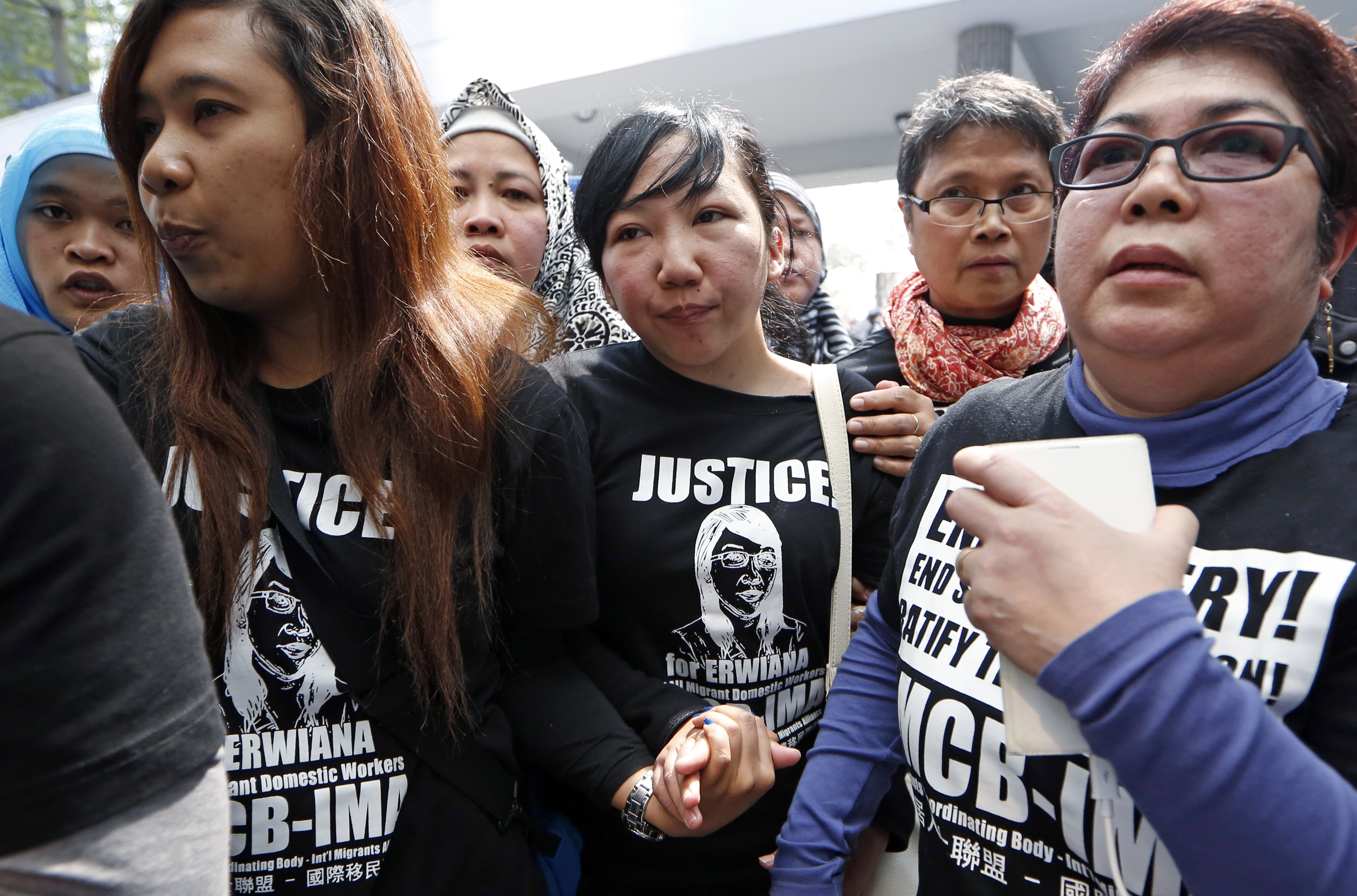 Indonesian maid Erwiana Sulistyaningsih, center, accompanied by her supporters, walks out from a court in Hong Kong on Feb. 10, 2015
