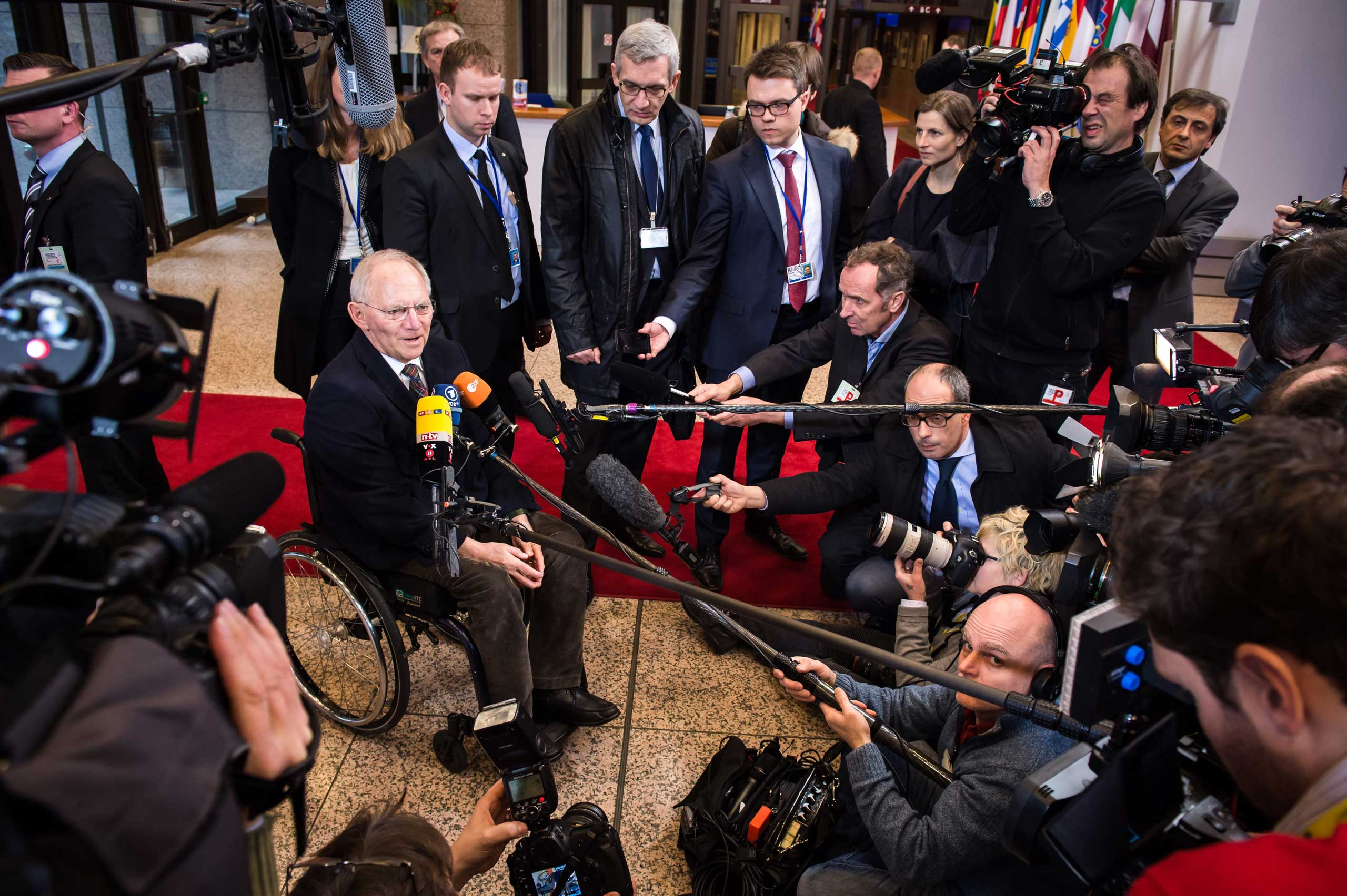 German Finance Minister Wolfgang Schaeuble, left, talks with journalists as he arrives for a meeting of Eurogroup finance ministers at the EU Council building in Brussels on Monday, Feb. 16, 2015.