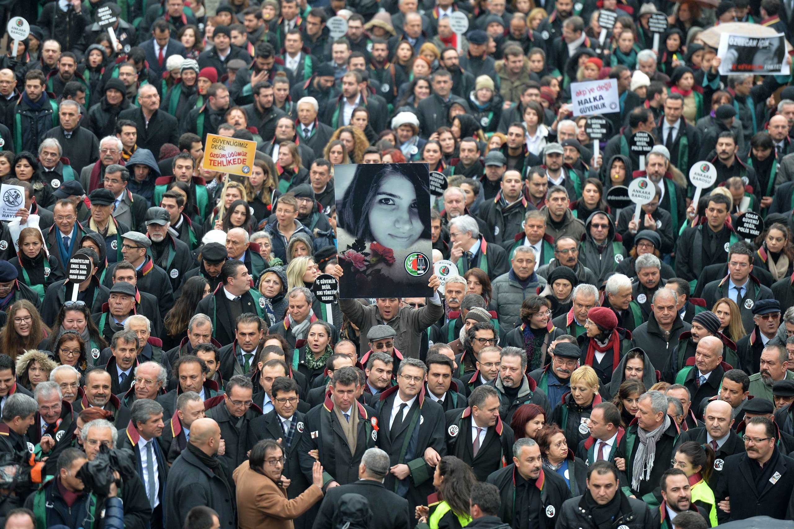 A man holds a poster depicting slain Ozgecan Aslan during a march of members of Turkey's Bar Association in Ankara, on Feb. 16, 2015 to protest against a law that strengthens the police's power.