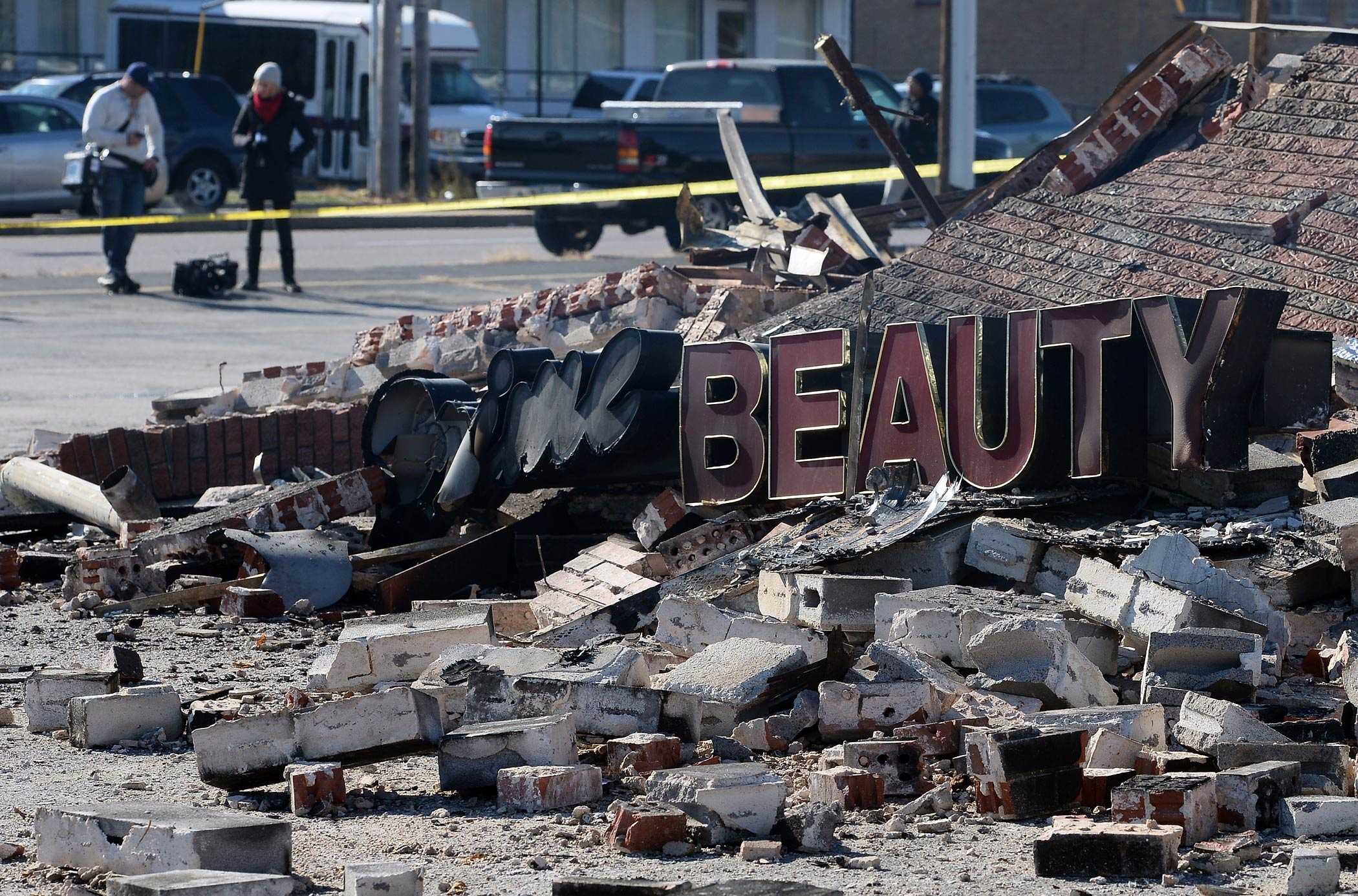 People walk past a collapsed building where protesters and looters rampaged businesses following the grand jury decision of Michael Brown, in Ferguson, Mo., on Nov. 25, 2014.