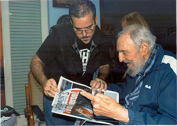 Former Cuban President Fidel Castro and President of Cuba's University Students Federation (FEU) Randy Perdomo look at a newspaper during a meeting in Havana on Jan. 23, 2015.