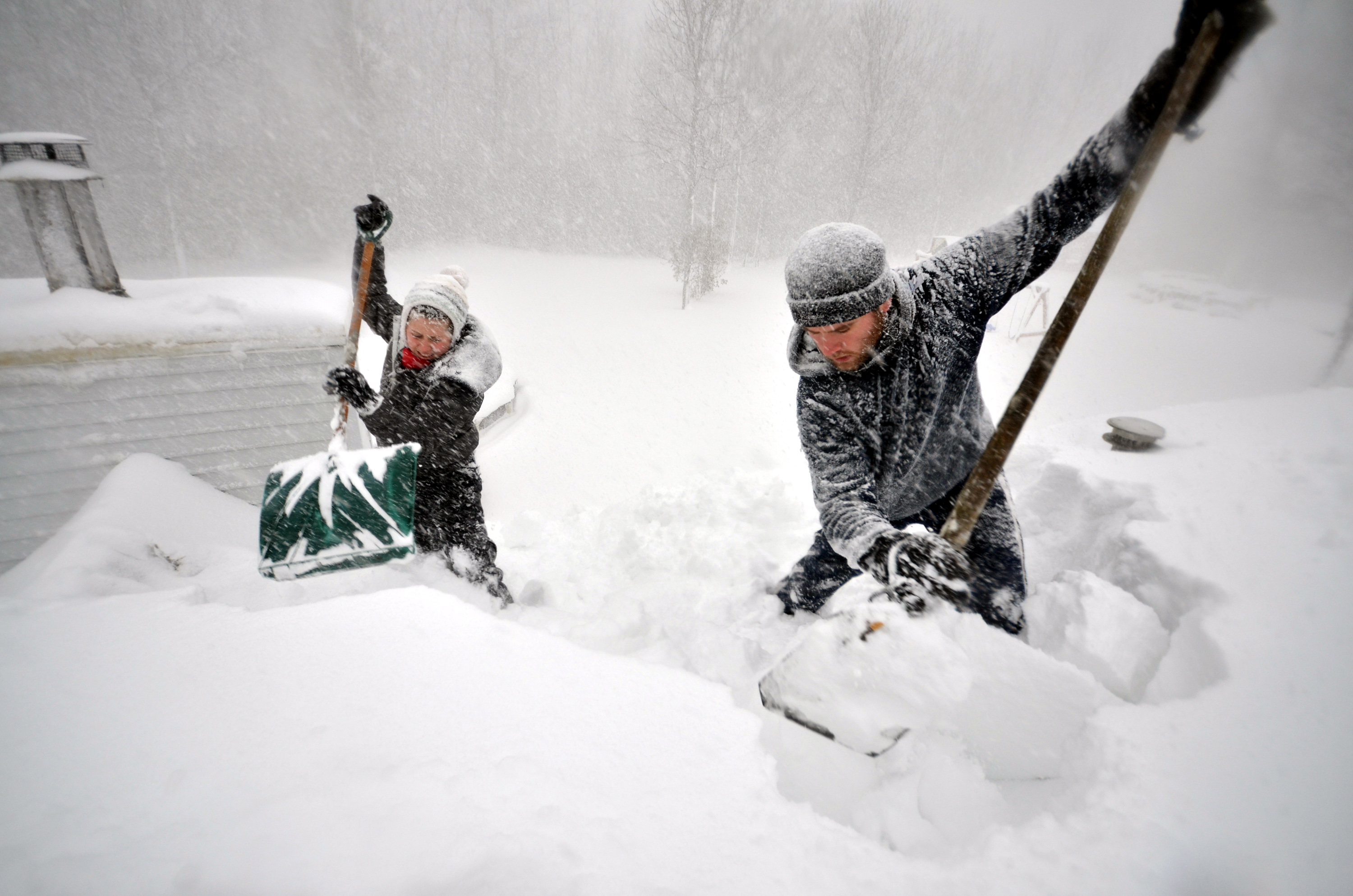 Tami Normile and Richard Brooks attempt to remove some of the five feet of snow from a roof top on November 20, 2014 in the Lakeview neighborhood of Buffalo, New York.