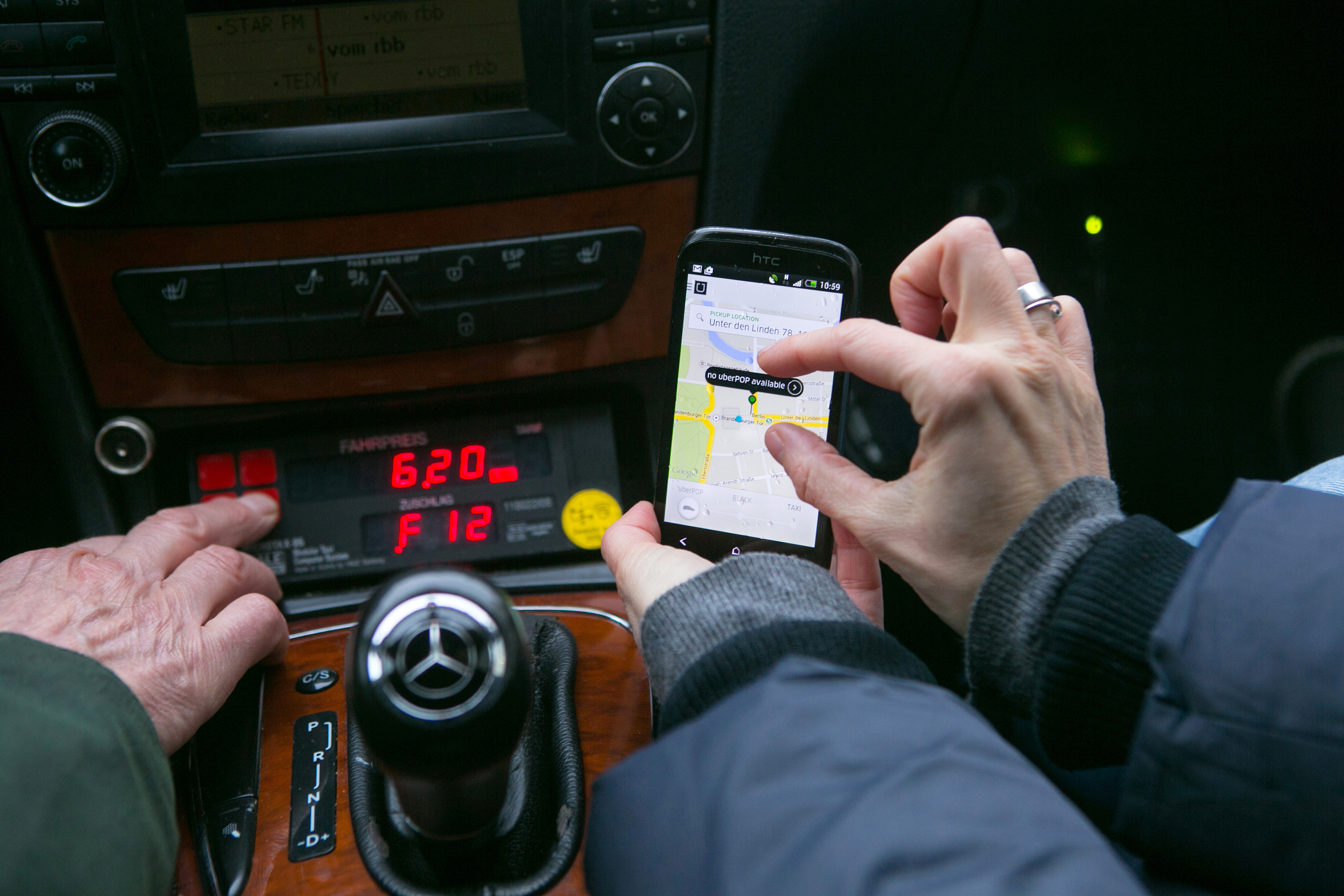 A passenger holds a HTC Corp. smartphone displaying the Uber Technologies Inc. car service application (app) as they sit in a taxi in this arranged photograph in Berlin, Germany, on Monday, Nov. 24, 2014.