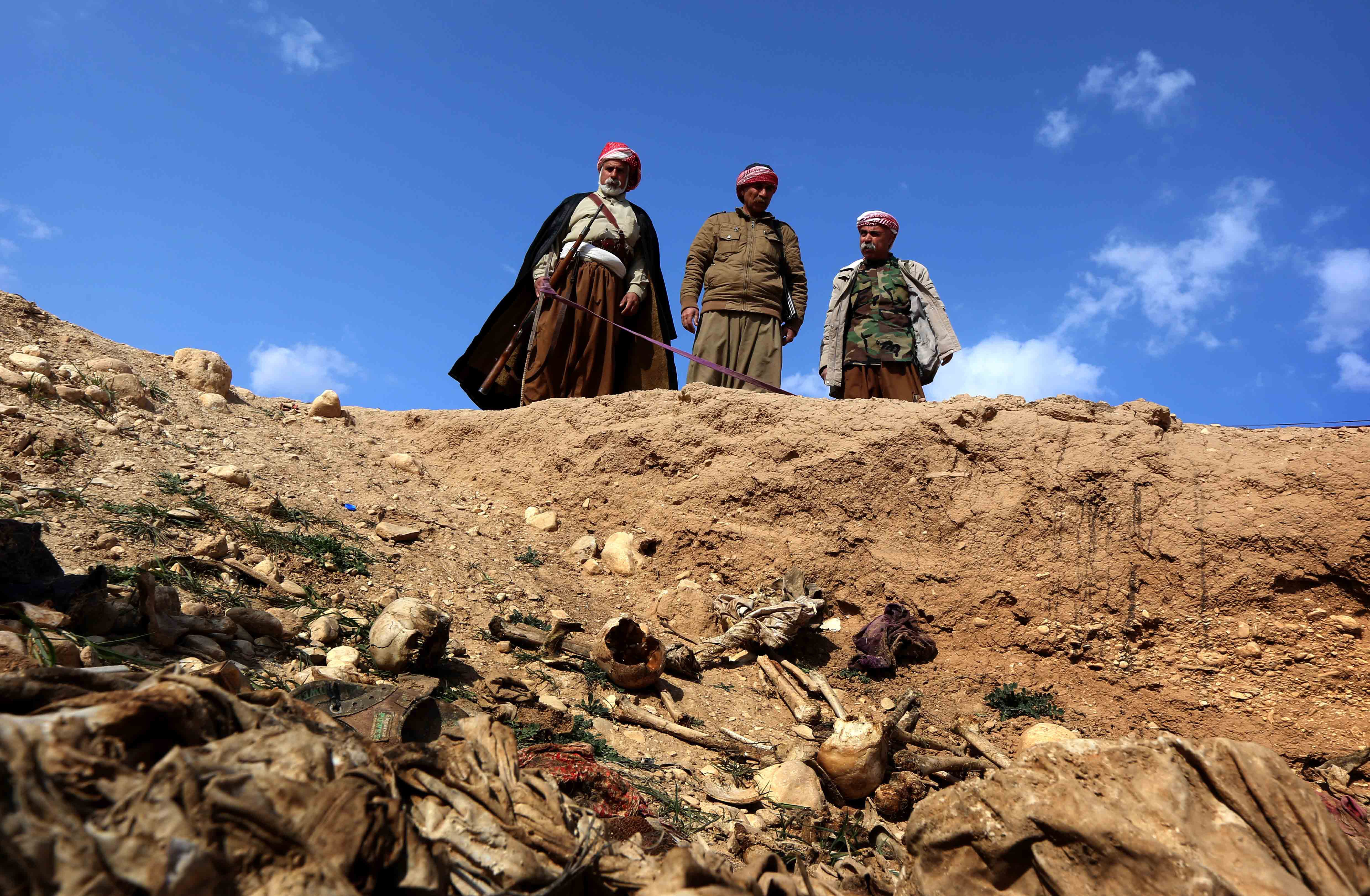 Members of the Yazidi minority search for clues on February 3, 2015, that might lead them to missing relatives in the remains of people killed by the Islamic State (IS) jihadist group, a day after Kurdish forces discovered a mass grave near the Iraqi village of Sinuni, in the northwestern Sinjar area.