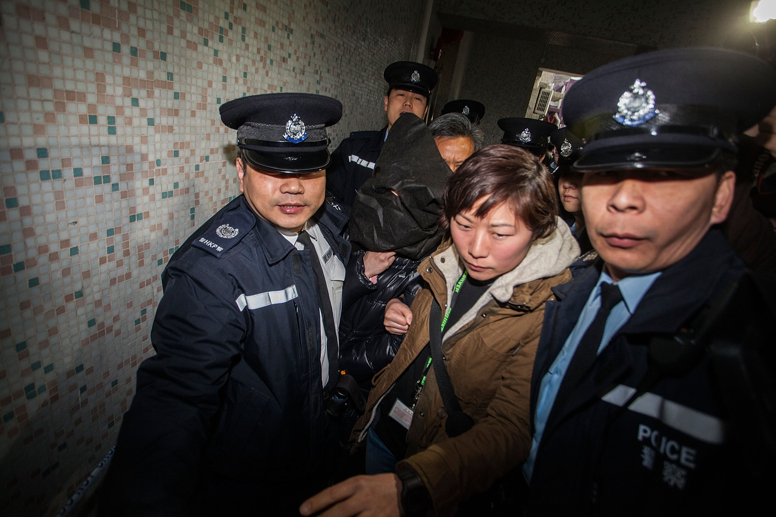 Police escort Law Wan-tung to her home for further investigation on Jan. 21, 2014, in Hong Kong