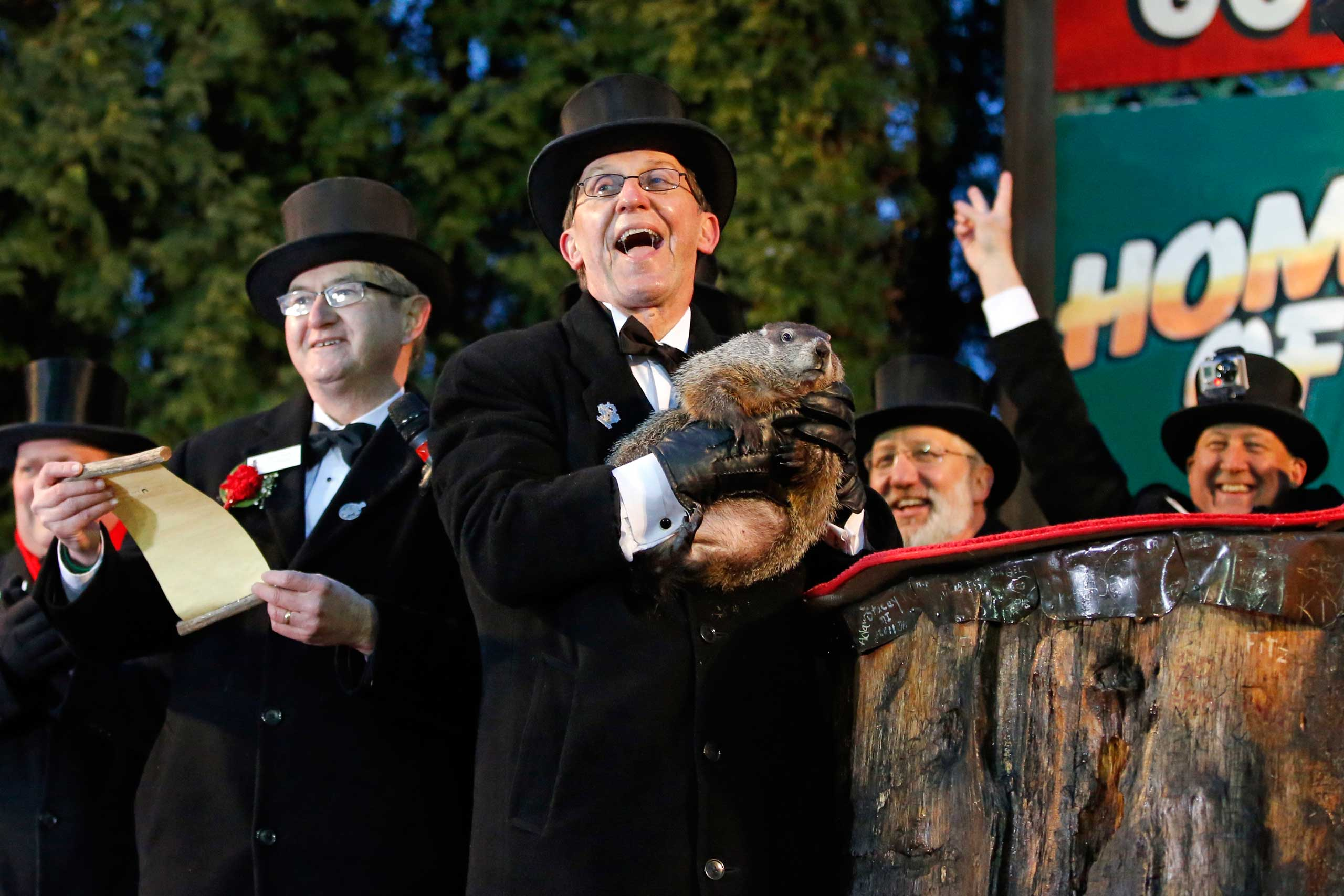 Groundhog Club handler Ron Ploucha, center, holds Punxsutawney Phil, the weather prognosticating groundhog, during the 129th celebration of Groundhog Day on Gobbler's Knob in Punxsutawney, Pa., Feb. 2, 2015.
