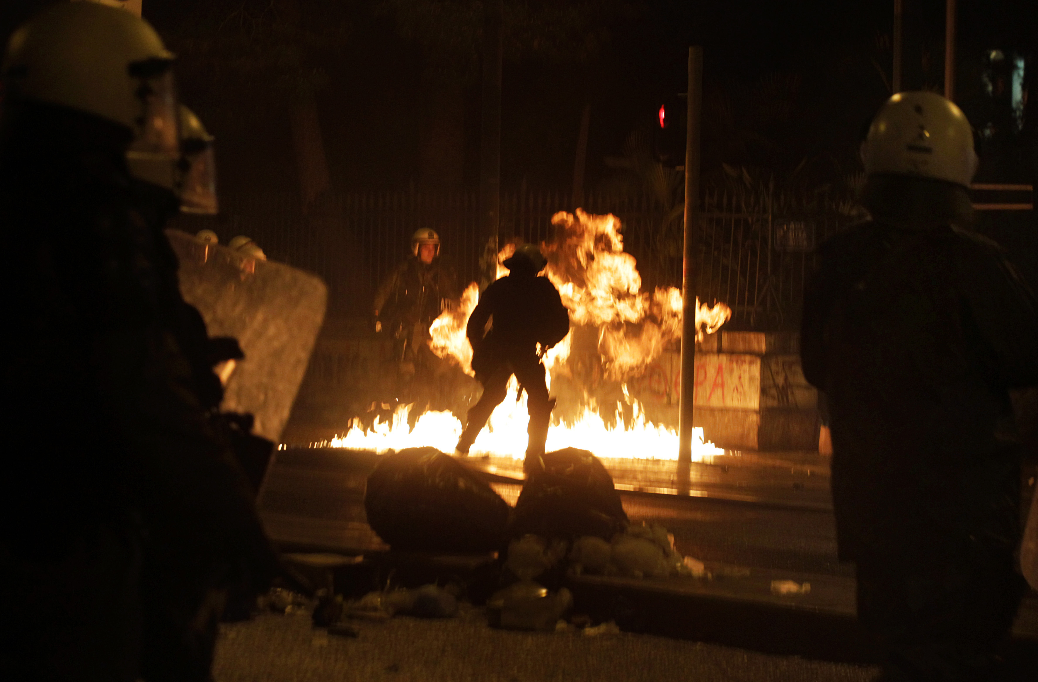 Riot policemen try to avoid a molotov cocktail during clashes after the end of an antigovernment protest called by leftist groups in Athens on Feb. 26, 2015