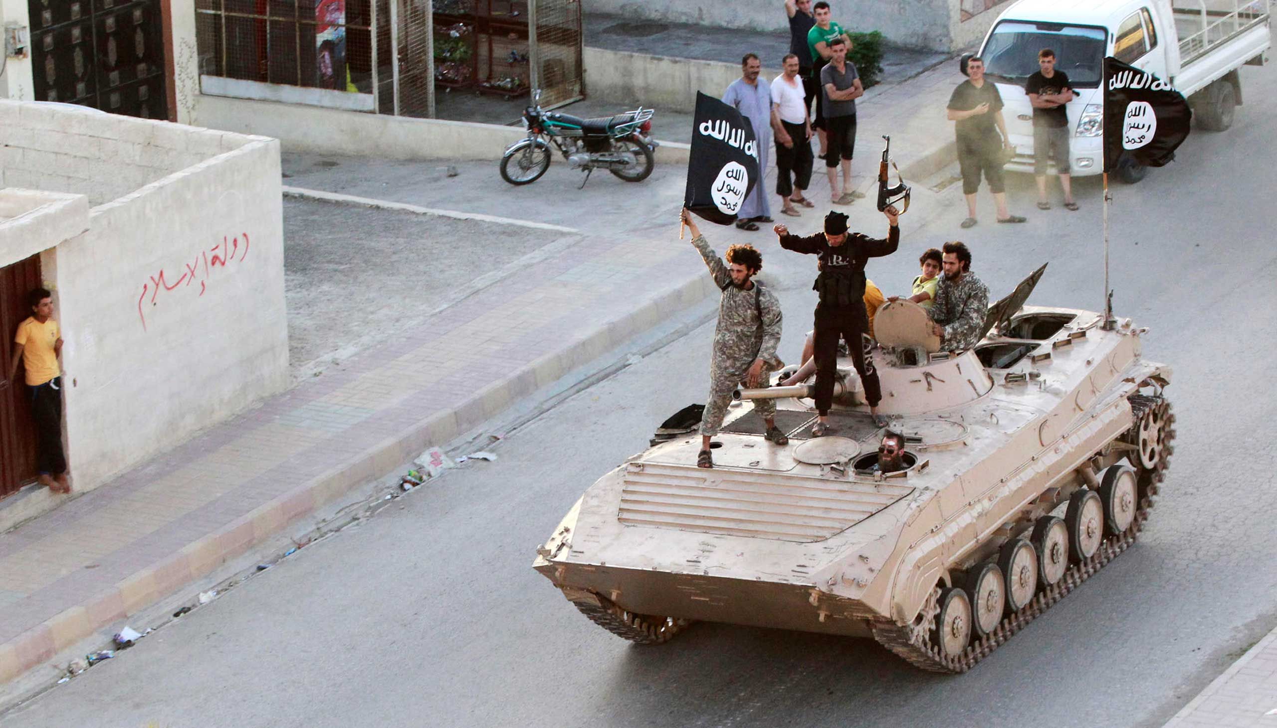Militant Islamist fighters take part in a military parade along the streets of northern Raqqa province, June 2014.
