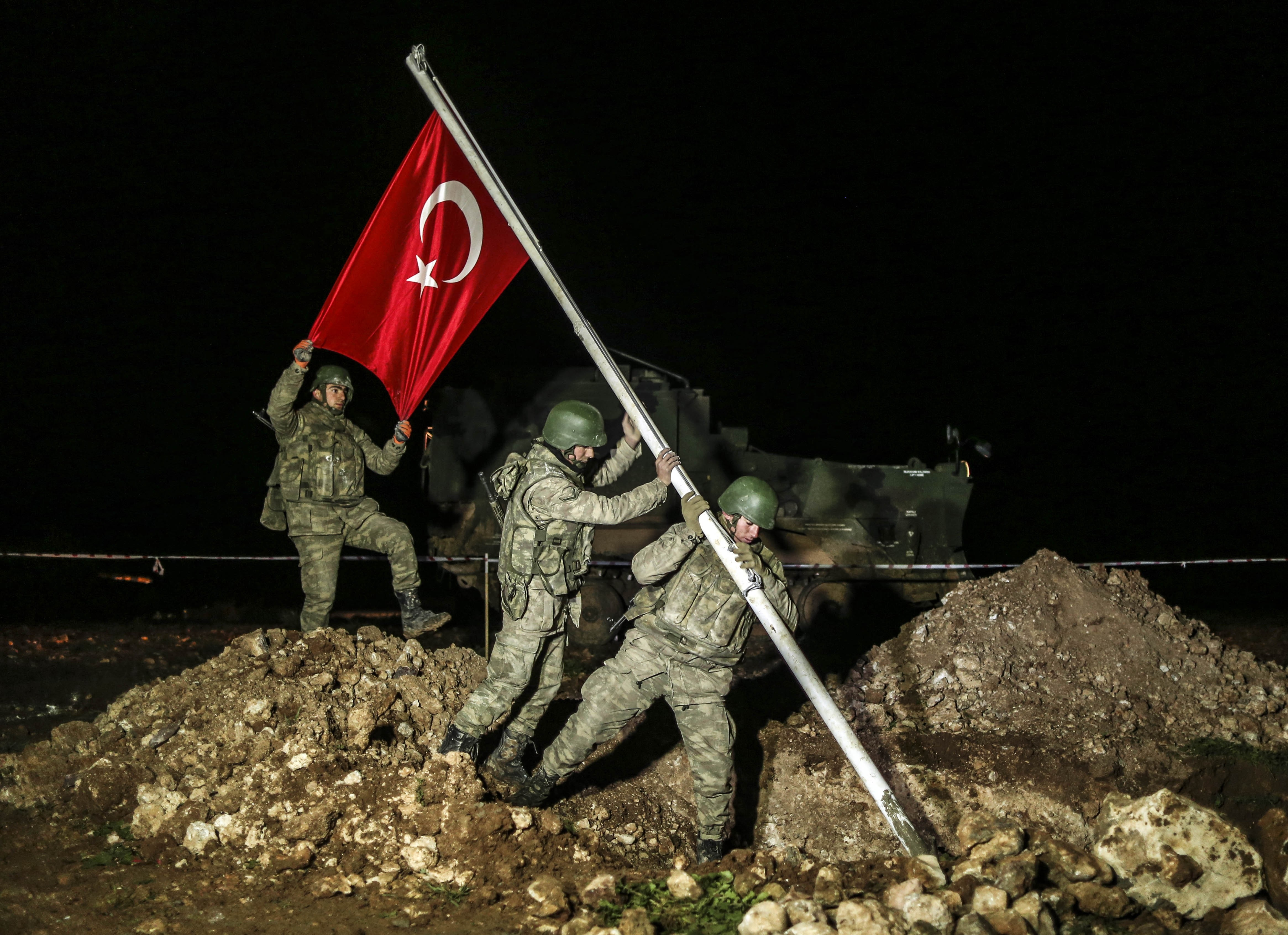 Turkish soldiers put a wire fence around area after Turkish flag is raised on Feb. 22, 2015 in the Esme region of Aleppo where the Tomb of Suleyman Shah will be placed.