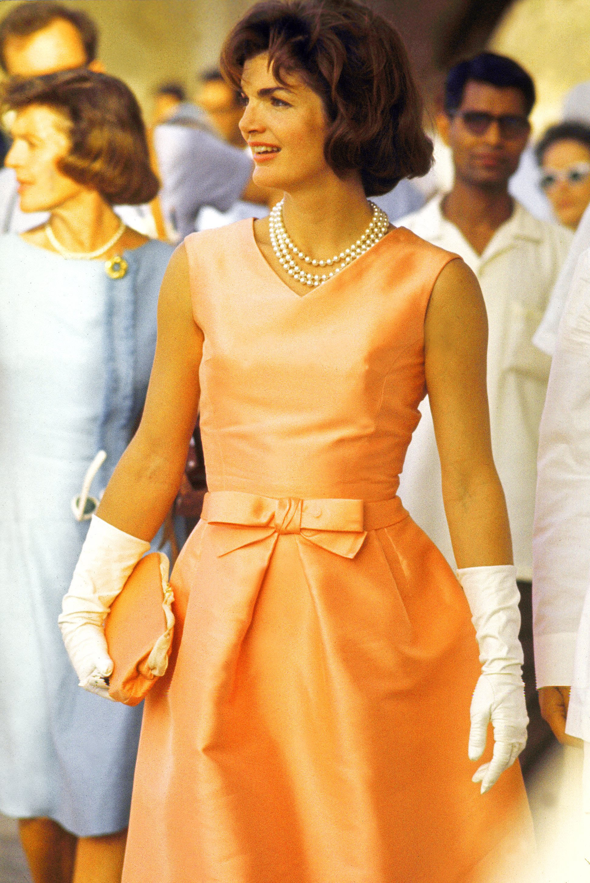 First Lady Jackie Kennedy wearing a fitted silk apricot dress and triple strand of pearls, walking through crowds at Udaipur during visit to India, 1962.