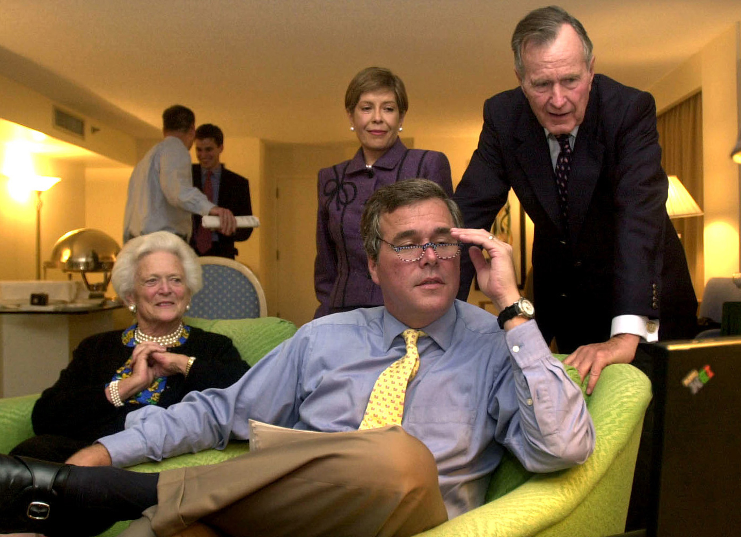 Republican governor of Florida, Jeb Bush, studies his laptop watching vote returns for his reelection his wife Columba Bush and his parents, former President George Bush and first lady Barbara Bush in Miami on Nov. 5, 2002.
