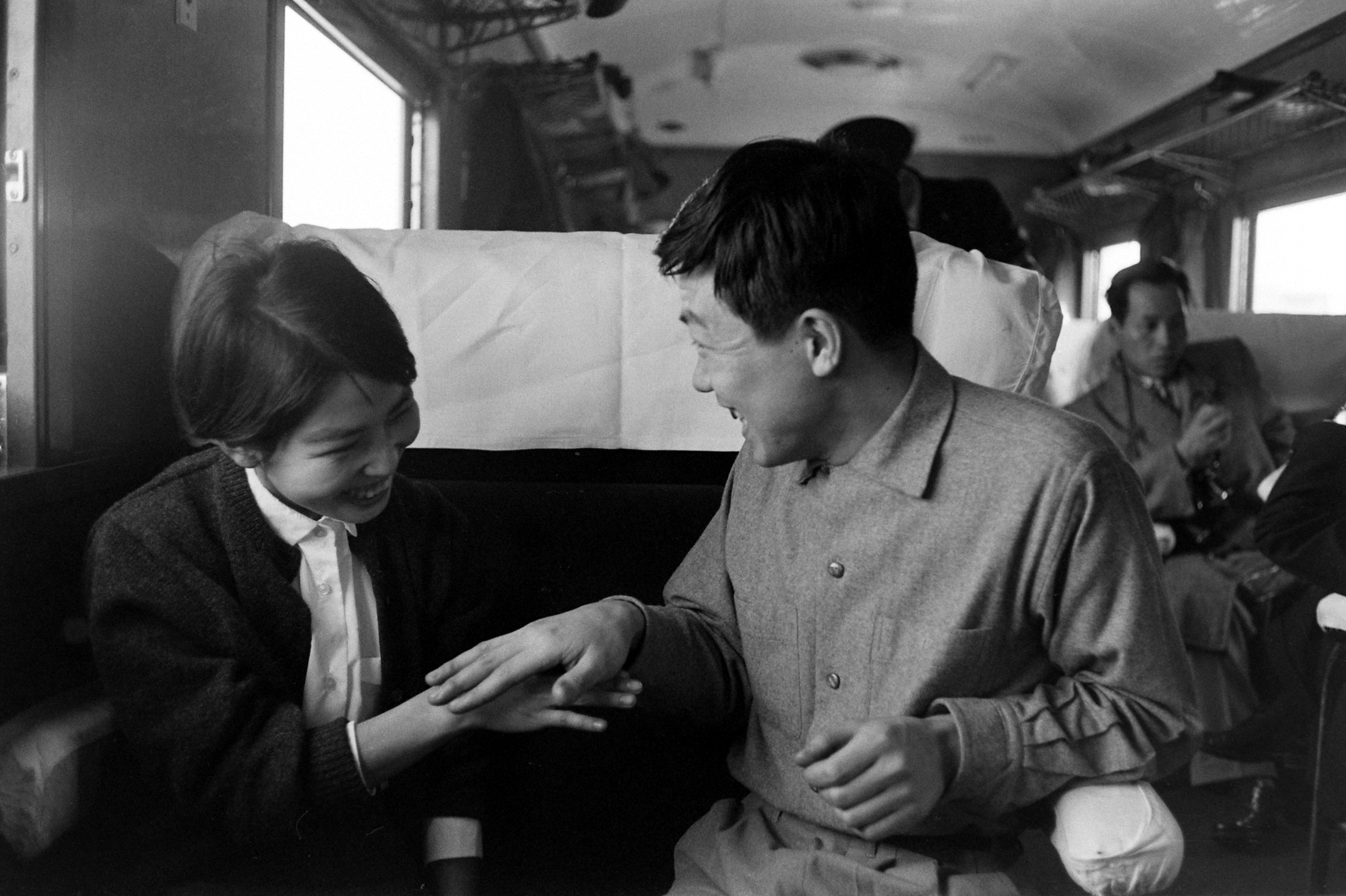 Chiyoko Inami, left, and her boyfriend, Akiksuke Tsutsui, playing a game on a train headed to Kyoto to meet Tsutsui's family.  March, 1959.