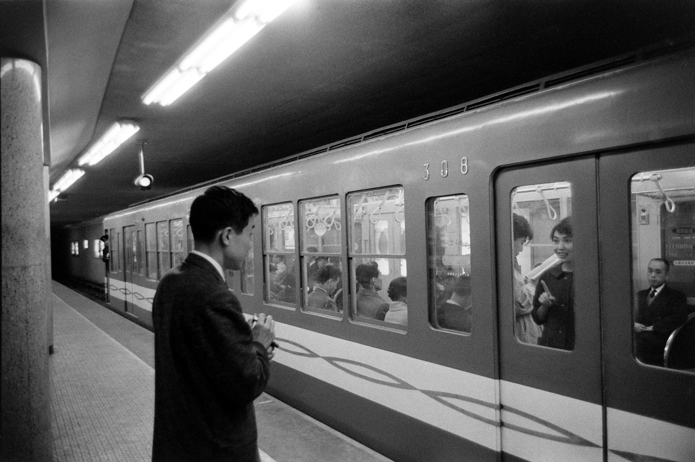 Akiksuke Tsutsui, left, bids his girlfriend, Chiyoko Inami, farewell as her train departs.  March 1959.